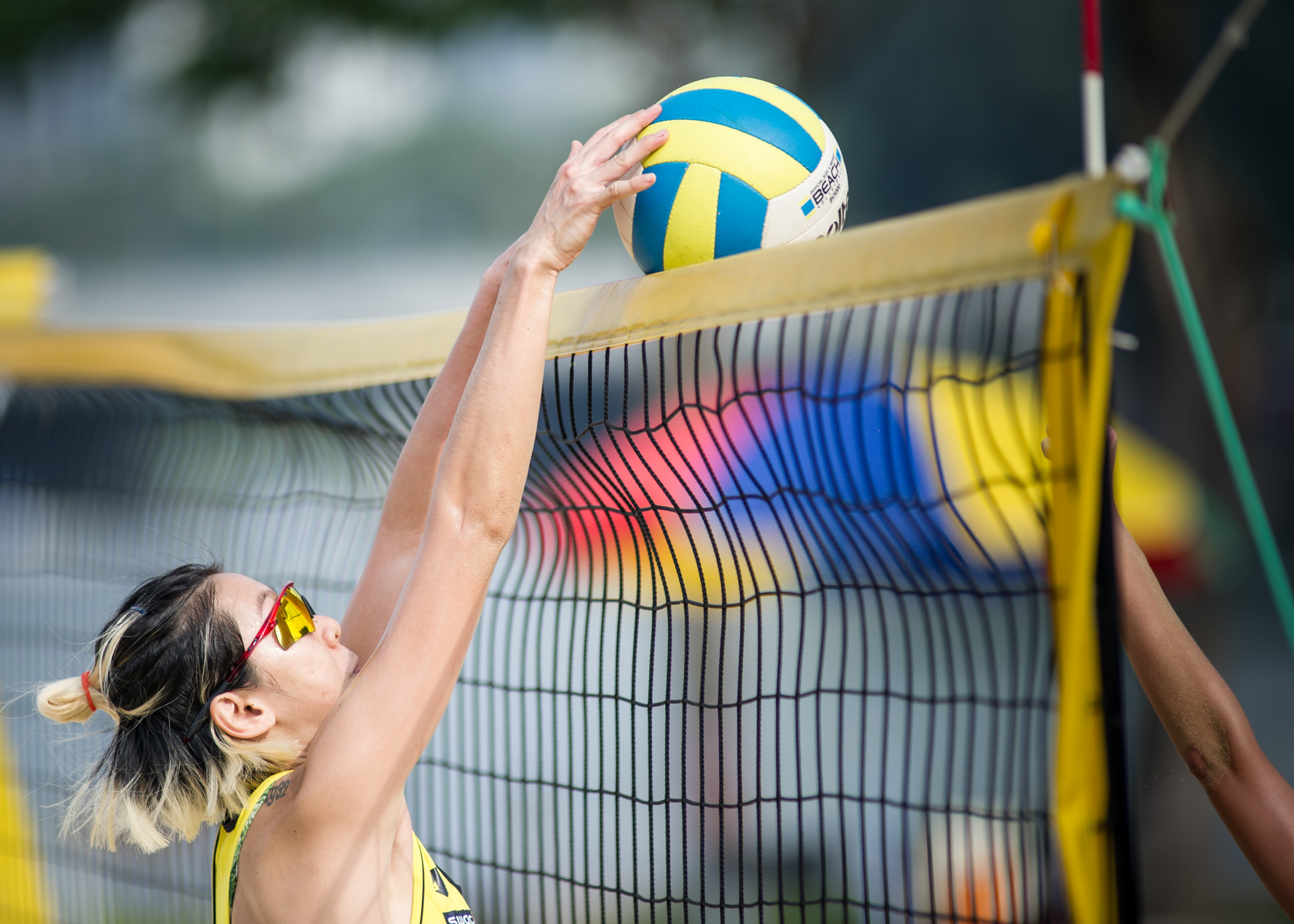 A player tips the ball over the net during the Beach Volleyball National Series at the Singapore Sports Hub.