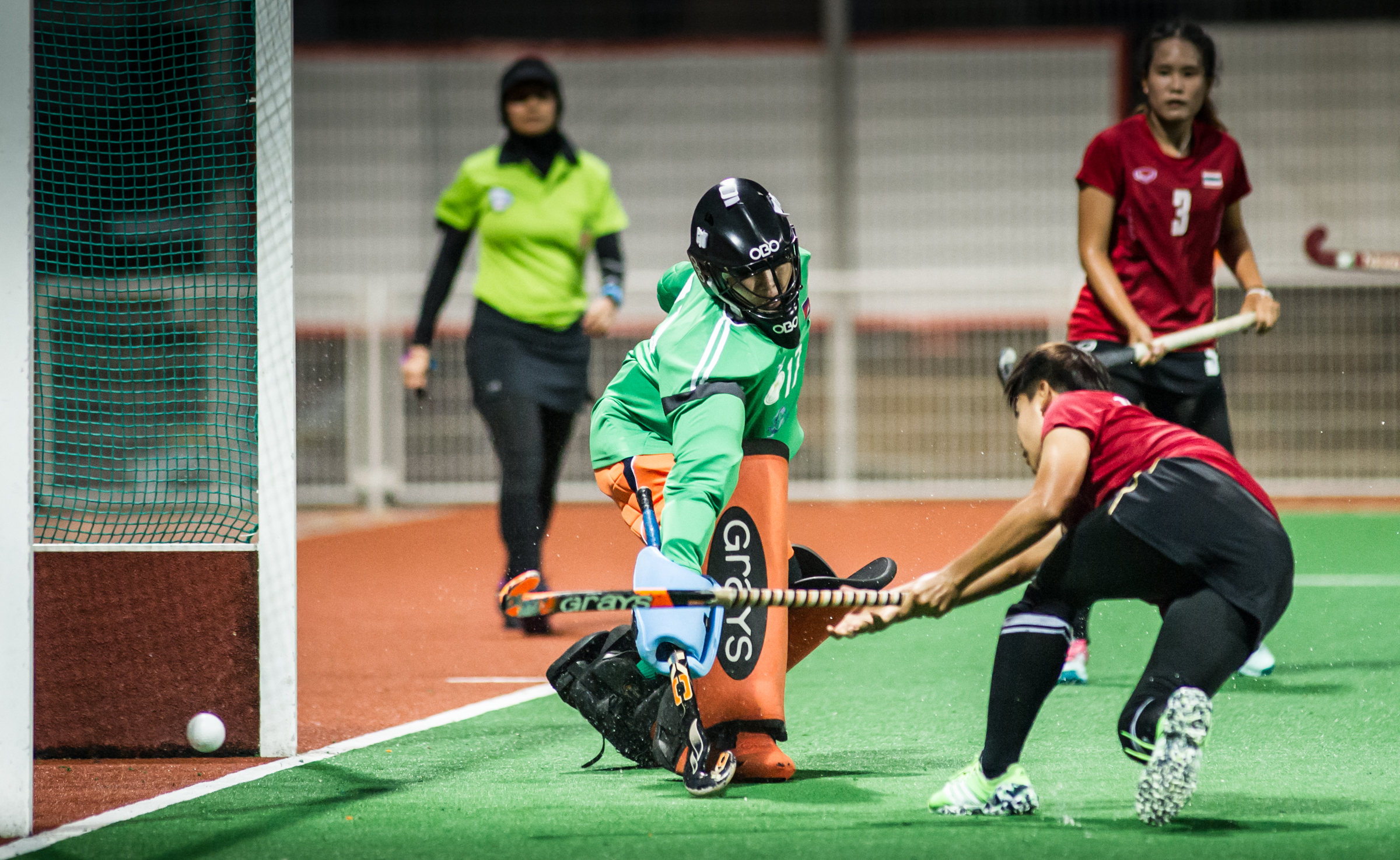 A Thai player shoots the ball past a Cambodian goal keeper during a World Hockey League match at the Sengkang Sports Complex.