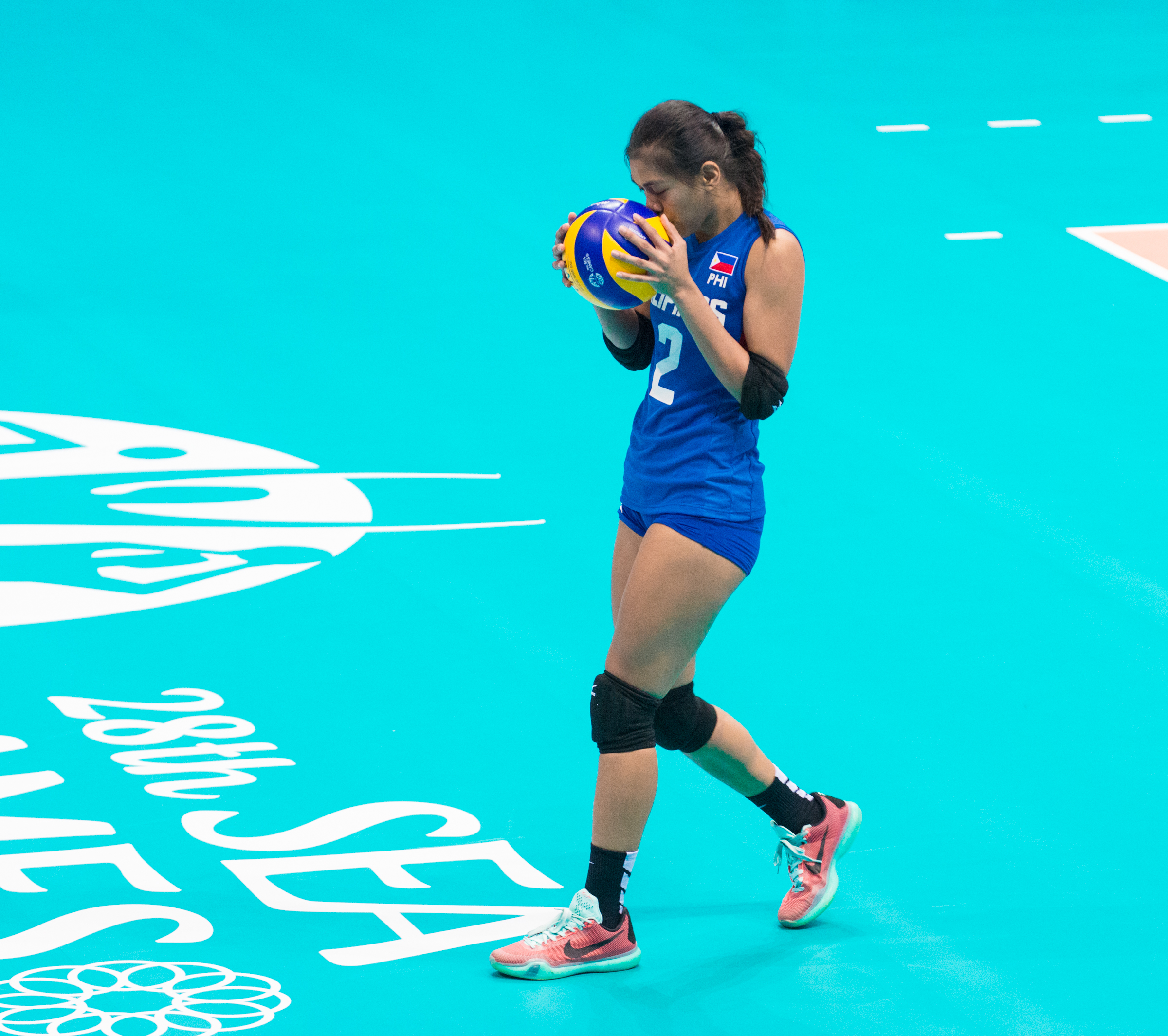 A Filipino player kisses the ball before a service during a match at the OCBC Arena.