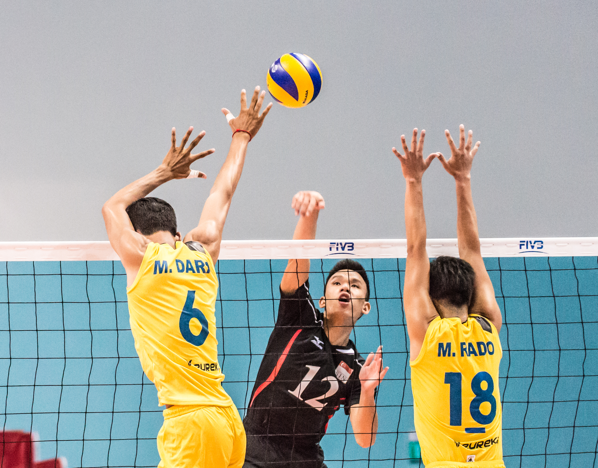 A Team Singapore player spikes the ball past two Cambodian players during a match at the OCBC Arena.