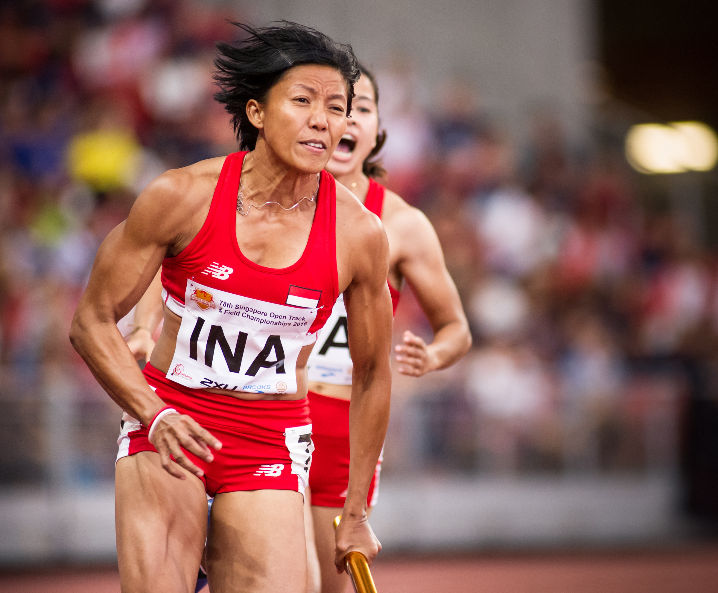 An Indonesian runner prepares to accelerate after receiving the baton in the 4 x 400 relay finals during the Singapore Open Track and Field Championships held at the Singapore Sports Hub.