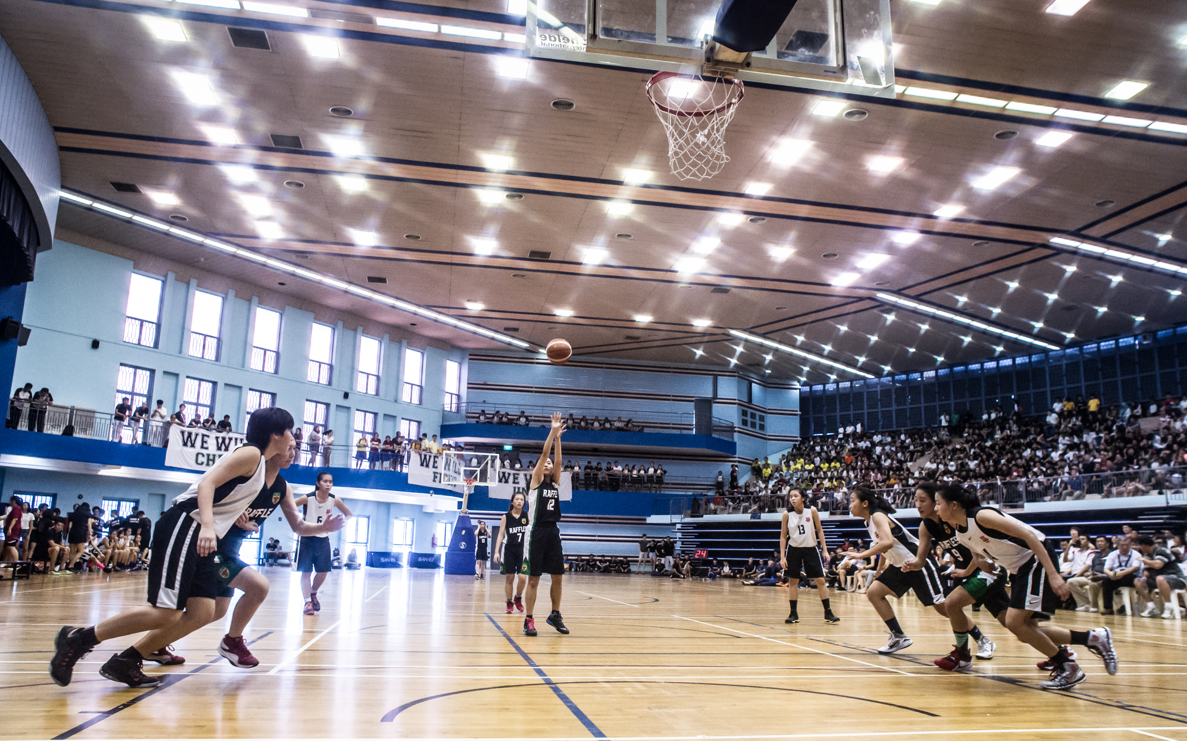 Basketball players rush forward during a free throw at a National Schools match at the Jurong East Sports Complex.