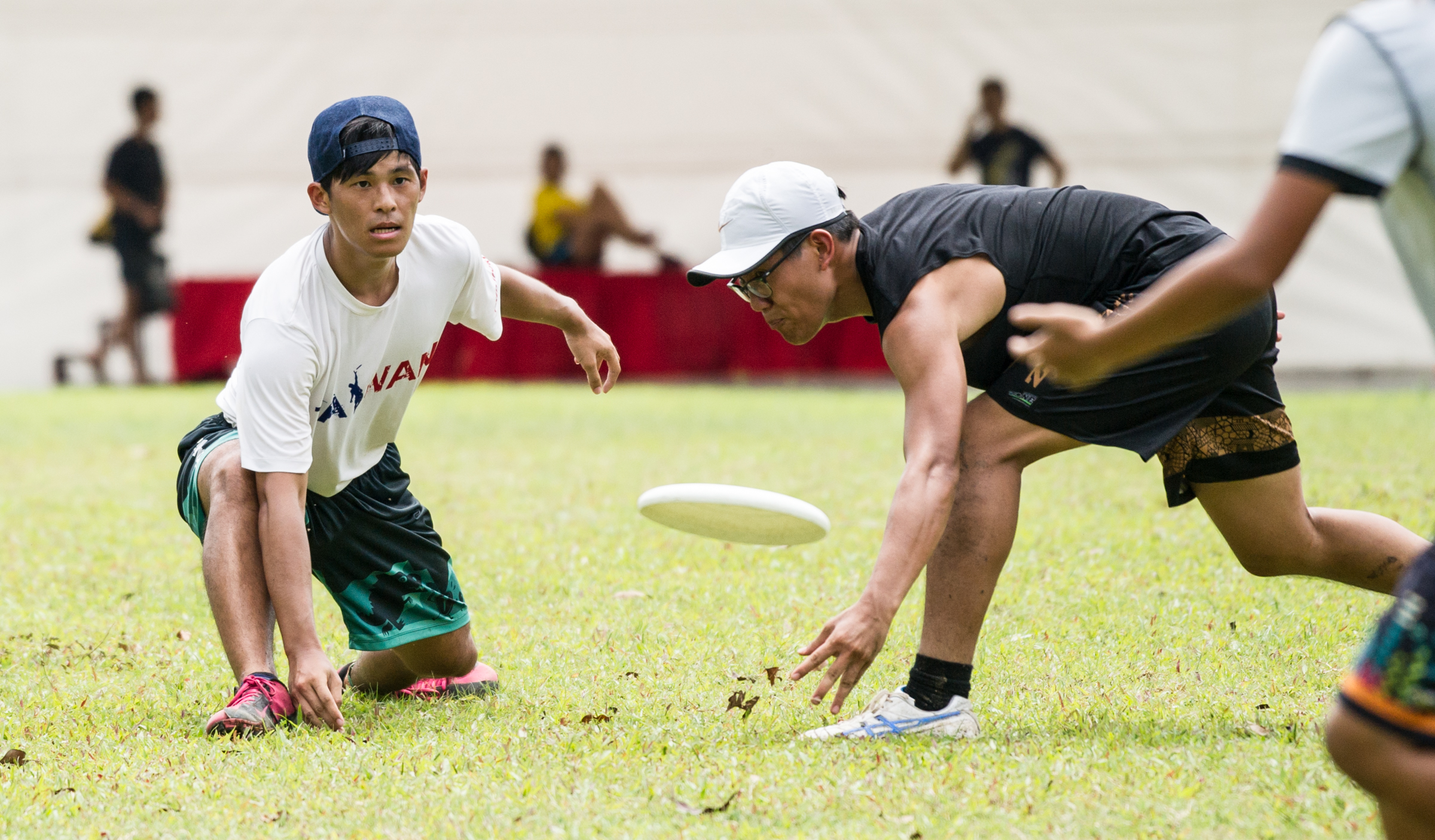 A player passes a frisbee past an opponent during a friendly at Ang Mo Kio Central.