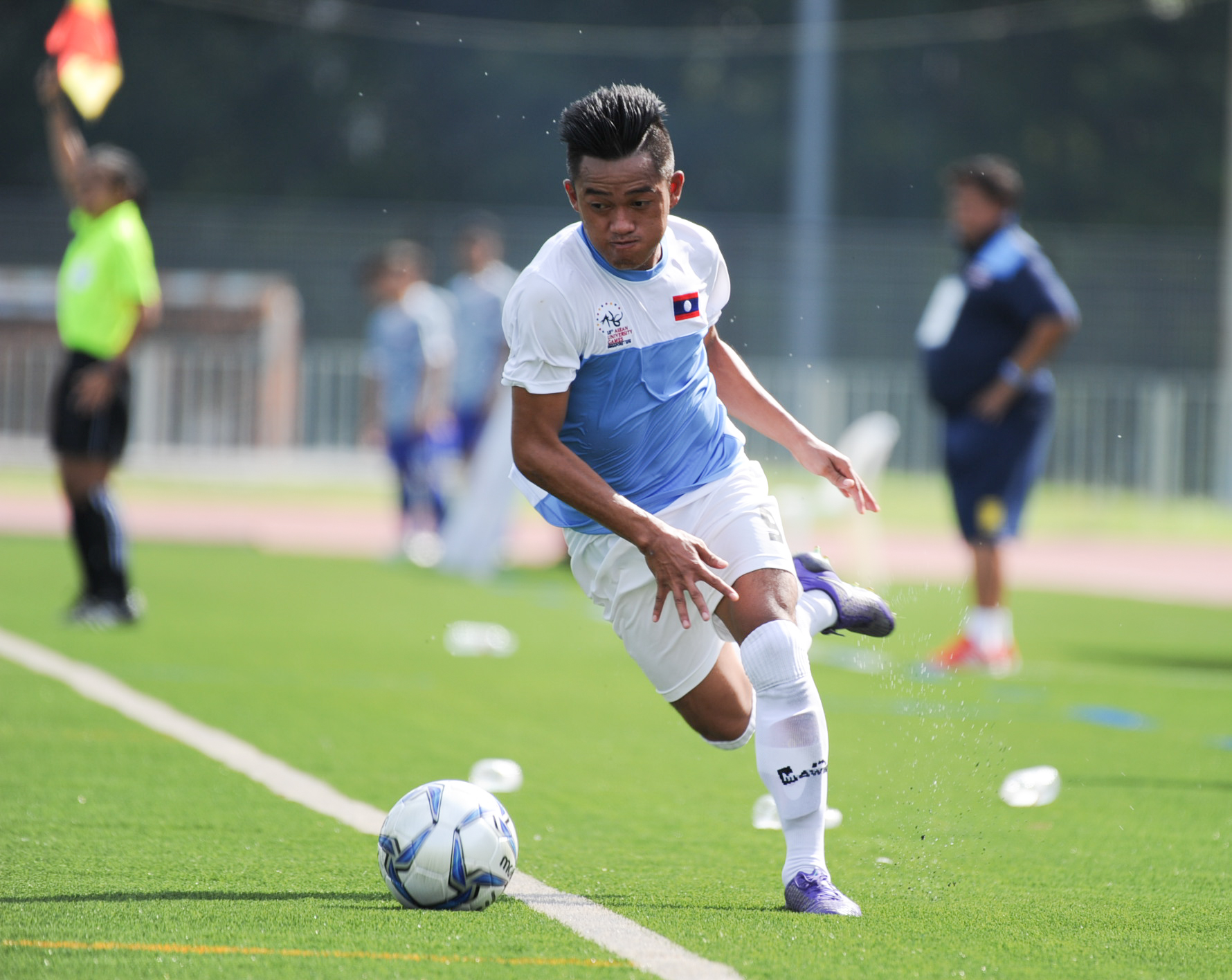 A Laotian player keeps the ball in play during the soccer competition of the ASEAN University Games at the Nanyang Technological University.