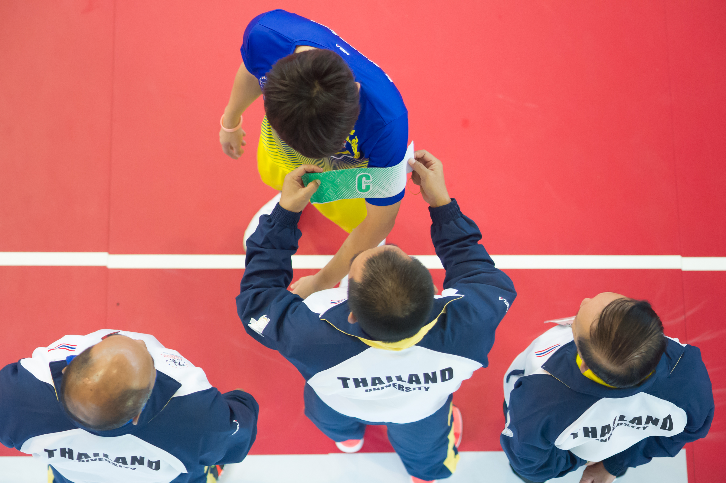 A Thai official puts on the captain armband for a player during the sepak takraw competition of the ASEAN University Games at the Bedok Sports Hall.