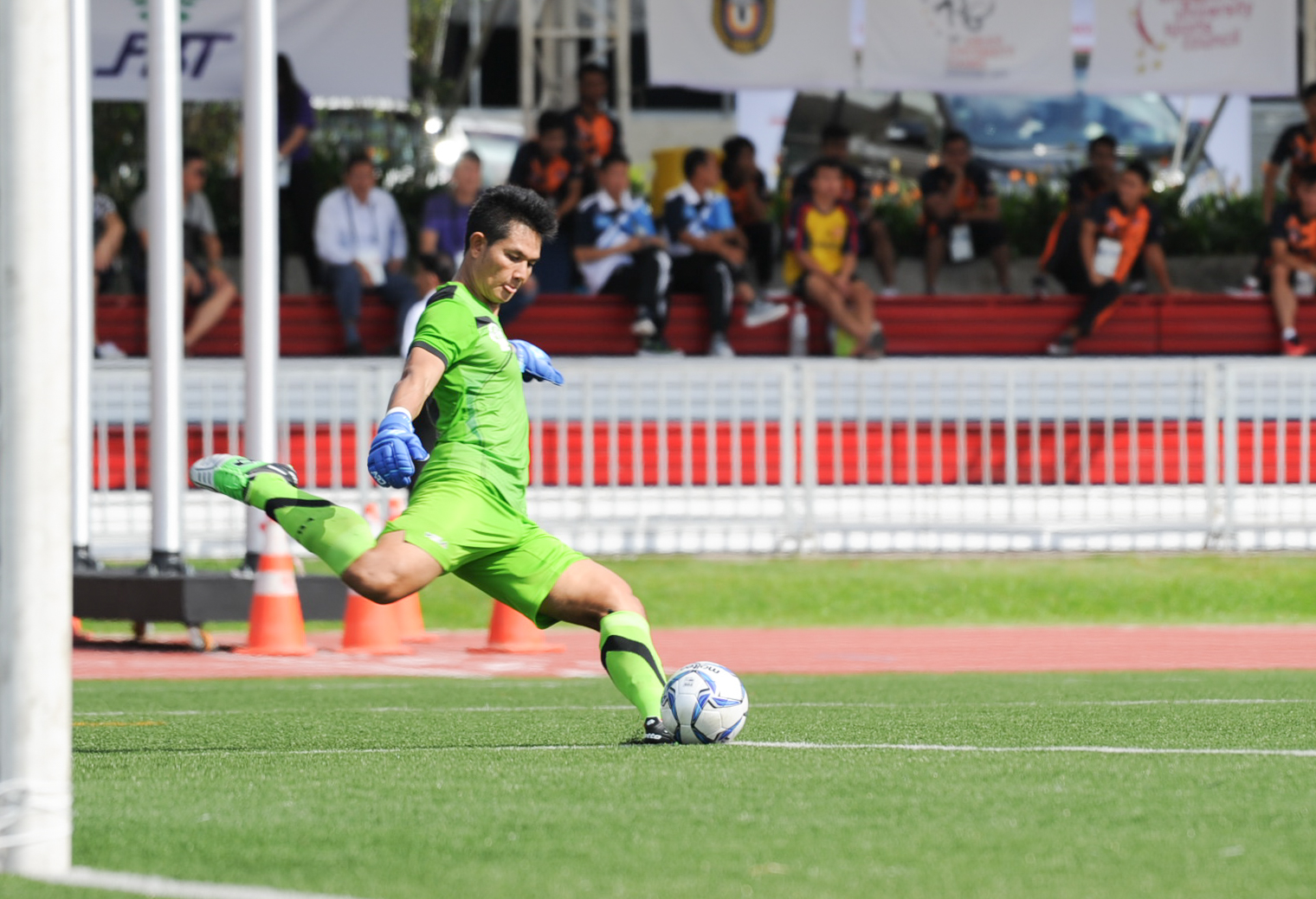 The Laotian goal keeper kicks the ball during the soccer competition of the ASEAN University Games at the Nanyang Technological University.