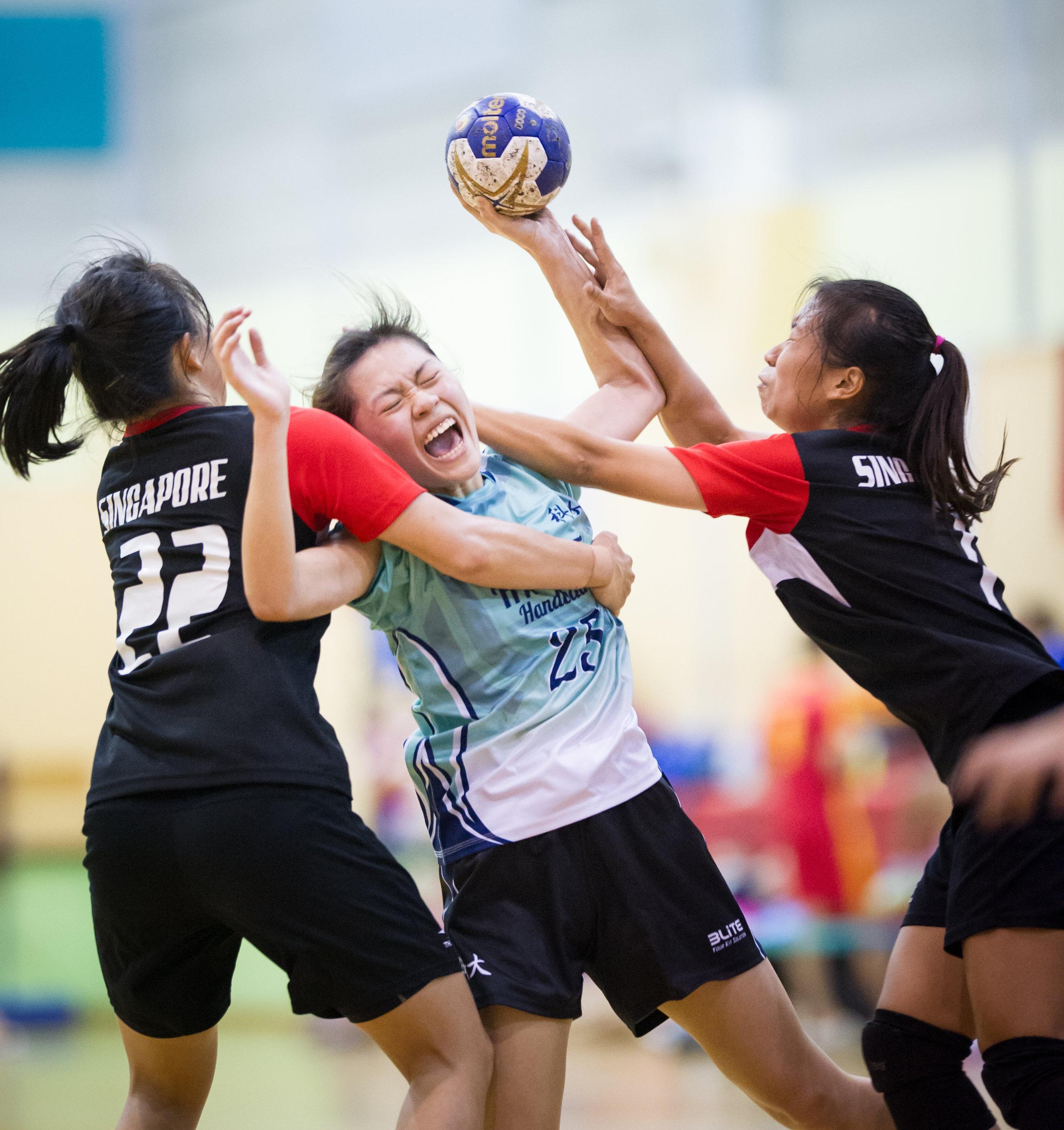 Singapore players block a Hong Kong player during an International hand ball match at the Sengkang Sports Complex.