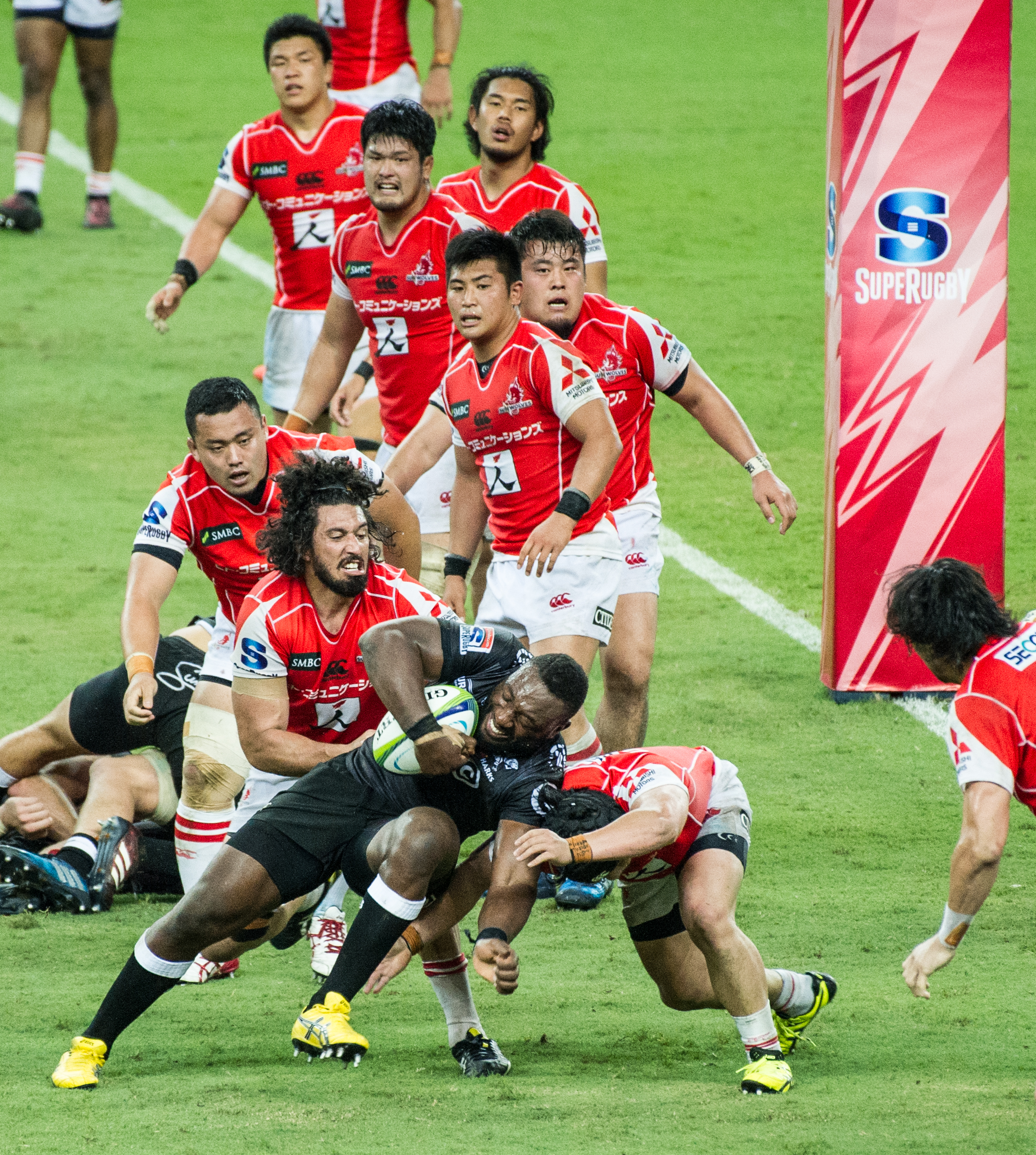 A South African player charges past a pack of Japanese players during a Super Rugby match at the Singapore Sports Hub.