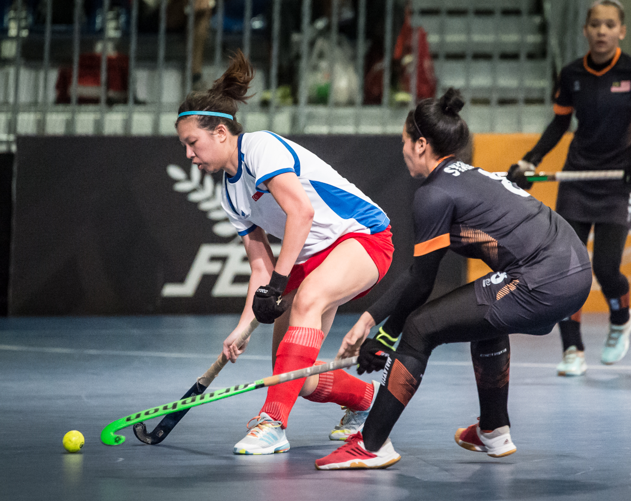 A Singaporean hockey player attempts to dribble past a Malaysian opponent during the SEA Games at the Malaysian International Trade and Exhibition Centre.