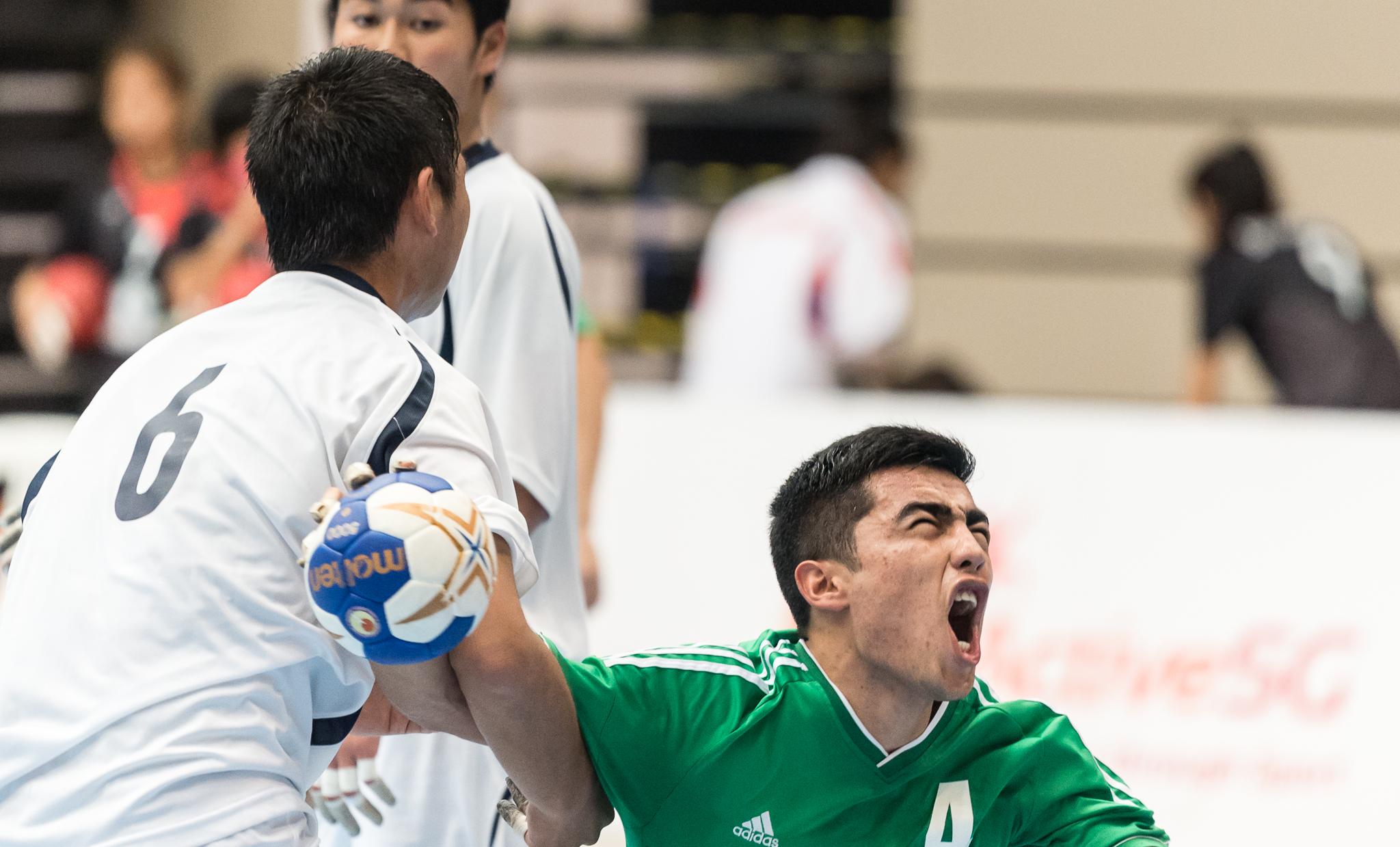 A Japanese player grabs an Uzbek player's arm during an International hand ball match at Our Tampines Hub.