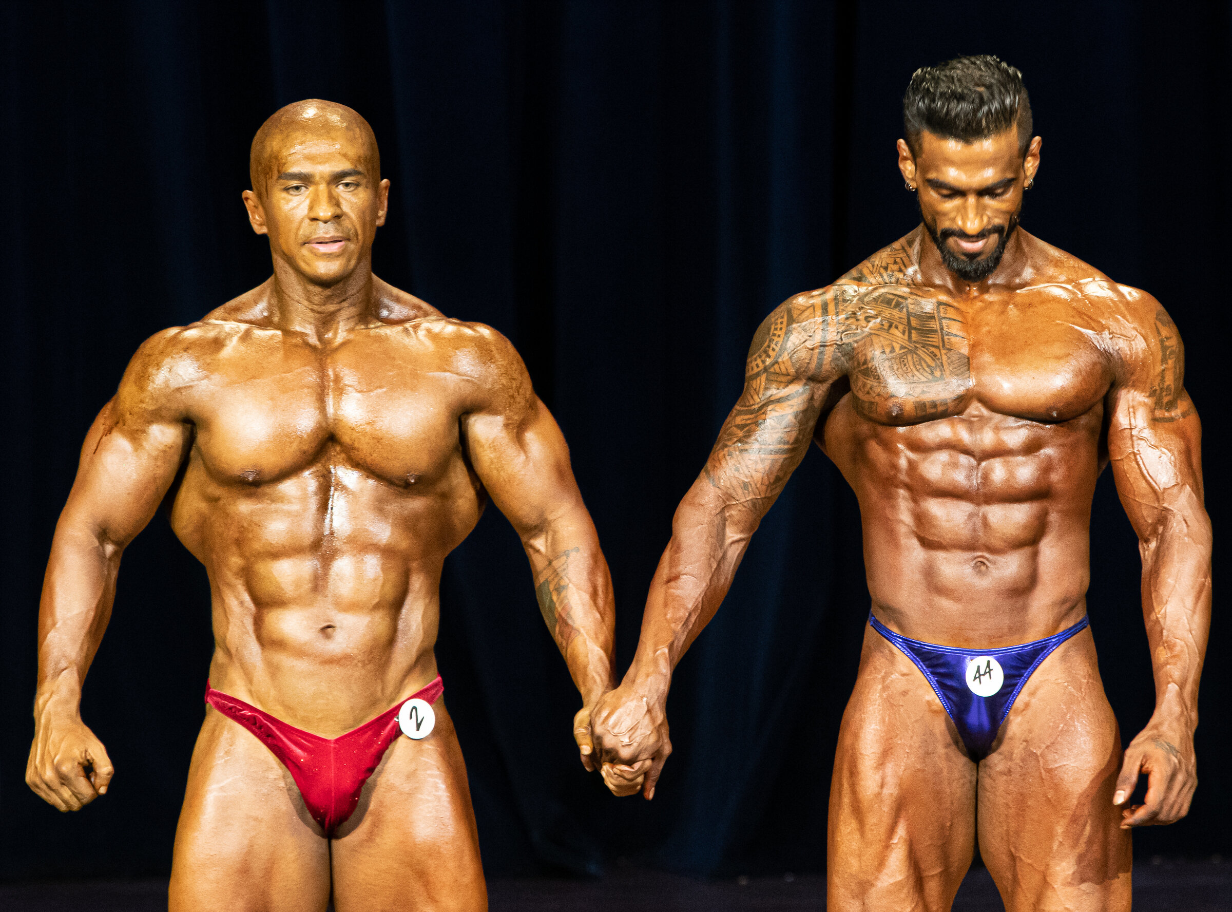A Panamanian and Malaysian competitor holds hands during the IFBB Regional Bodybuilding Finals at the Kreta Ayer People's Theatre.