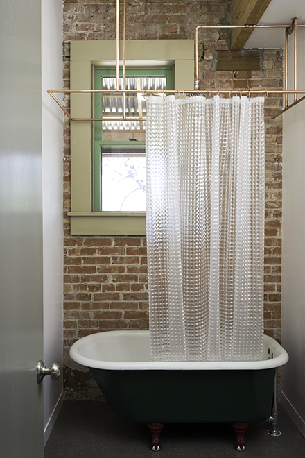"Rigid copper pipe shower curtain rod, vintage 1920's cast-iron bath tub, residential loft, ""El Picoso"", San Antonio, Texas, 2008. Photo by Chris Cooper Photography"