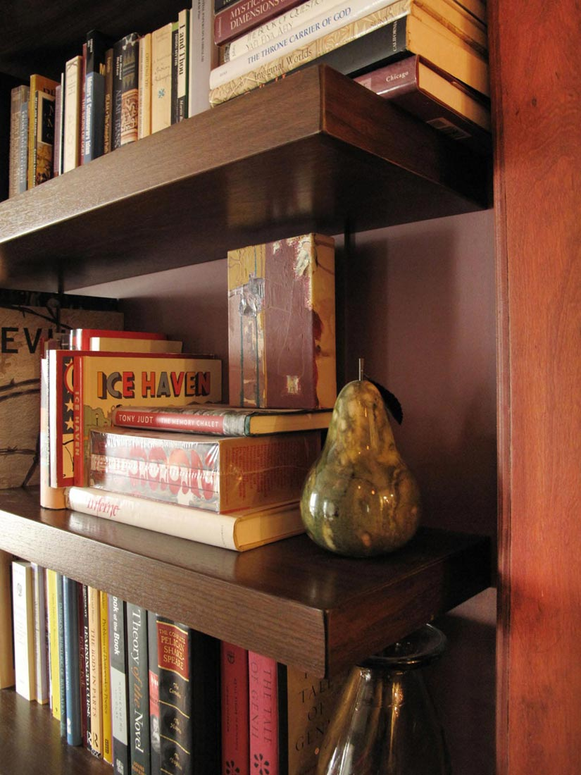 """These wall shelves are not truly """"floating,"""" but use thin metal straps for support. If you look closely, you can see one of the straps behind the pear."""
