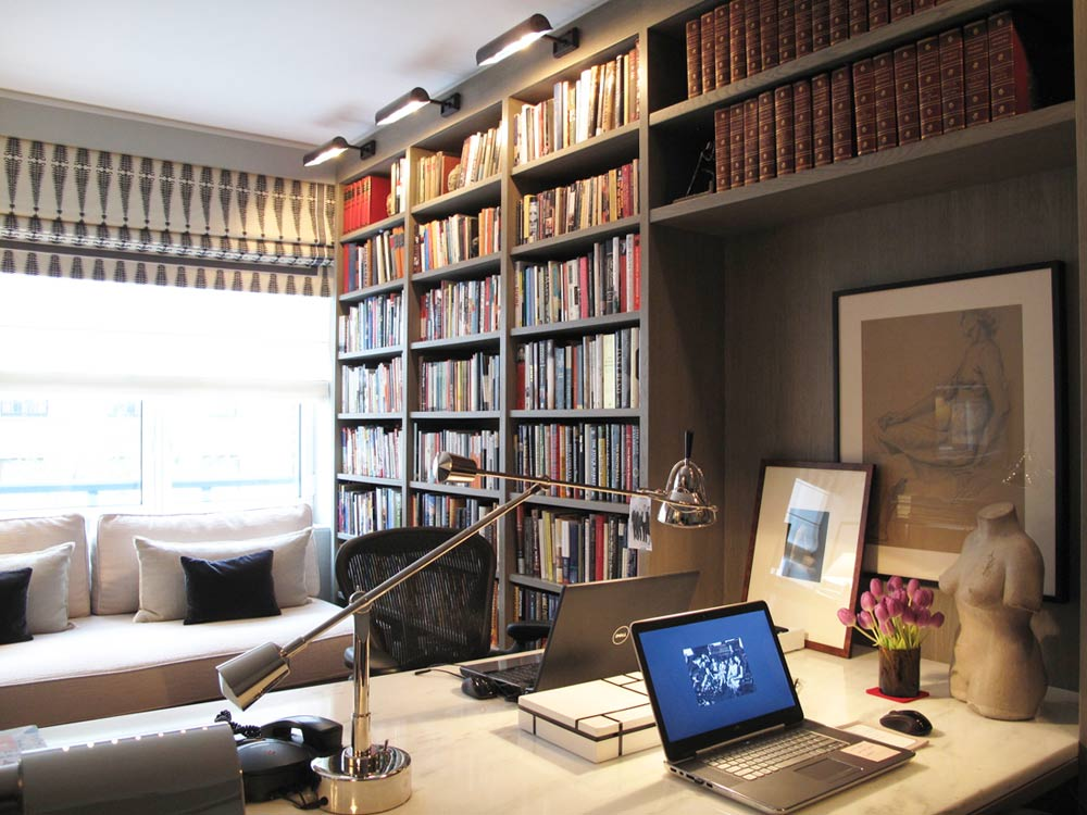 Custom floor-to-ceiling bookcases are lit up from above.