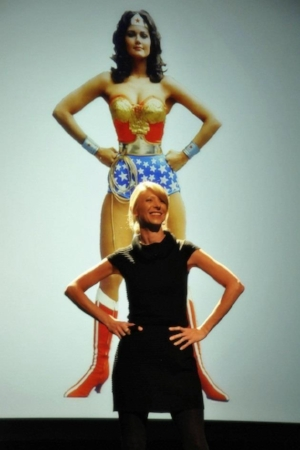 Professor Amy Cuddy demonstrating an expansive posture during a talk.