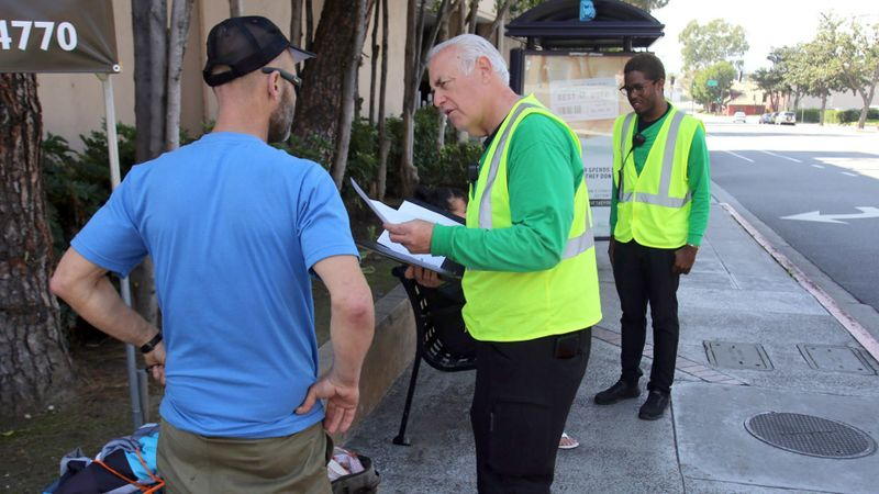 Bob Newman, ambassador manager, center, and La Quentan McGuire, ambassador team leader, help people in downtown Burbank, Downtown Burbank has a new program featuring ambassadors who assist locals and tourists with local activities. (James Carbone / Burbank Leader)
