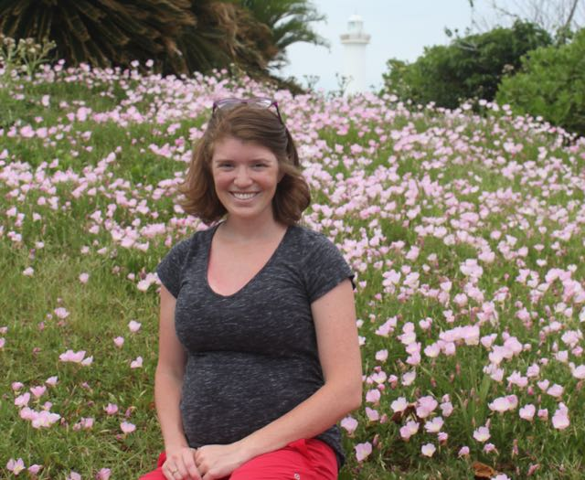 Image of Annie while pregnant sitting in a field of flowers in Okinawa, Japan.