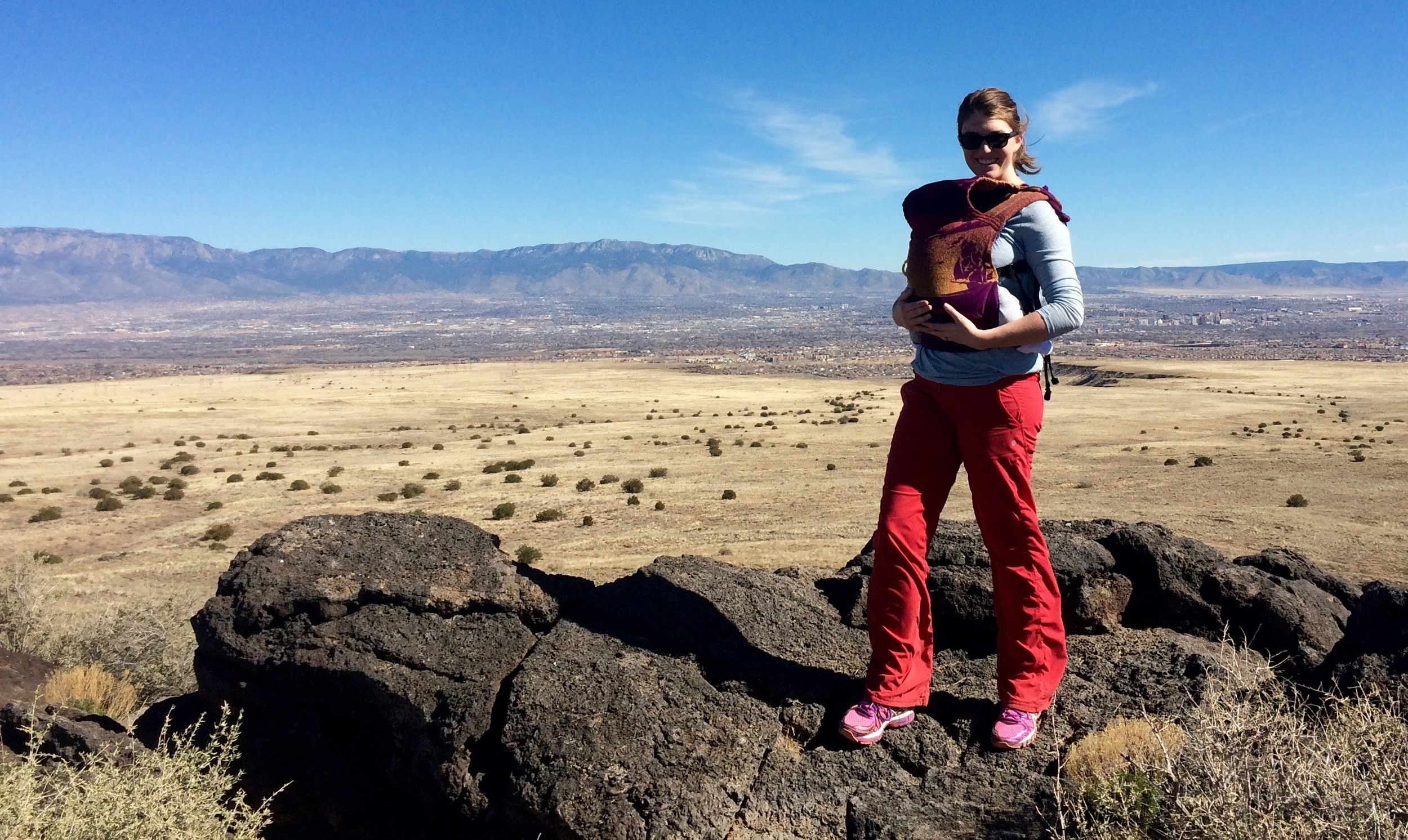 Image of Annie carrying her baby in a buckle carrier and standing on an extinct volcano in Albuquerque, NM.