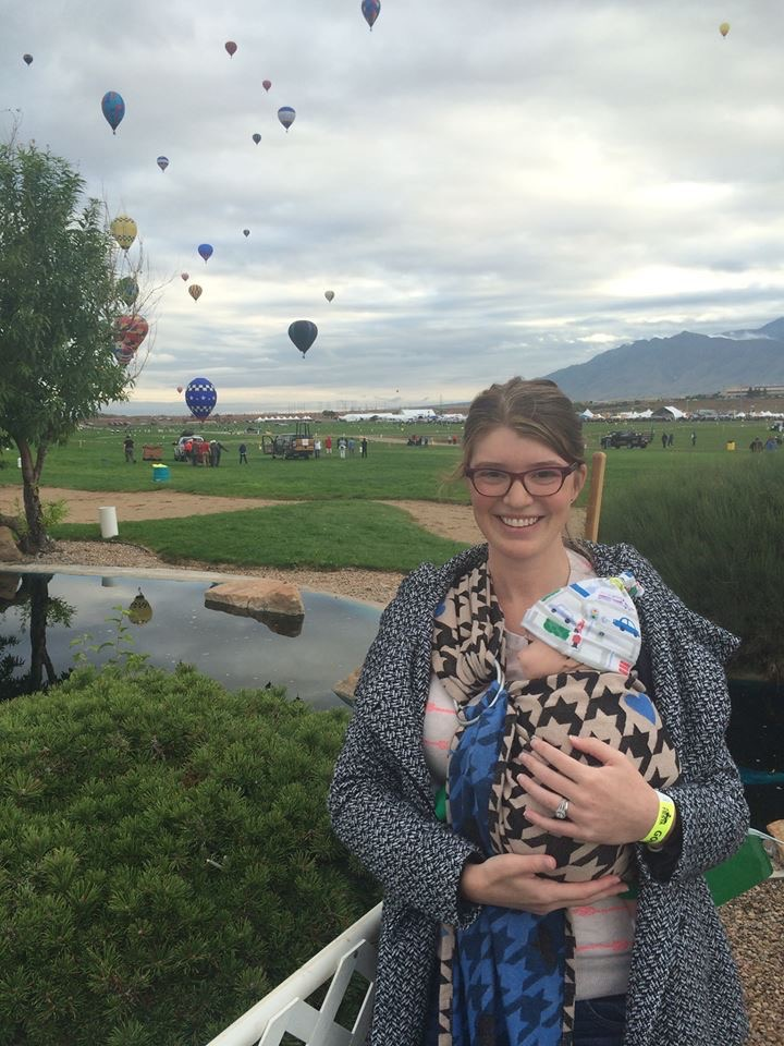 Annie at Albuquerque's Balloon Fiesta, holding her baby in a ring sling, standing in front of hot air balloons.