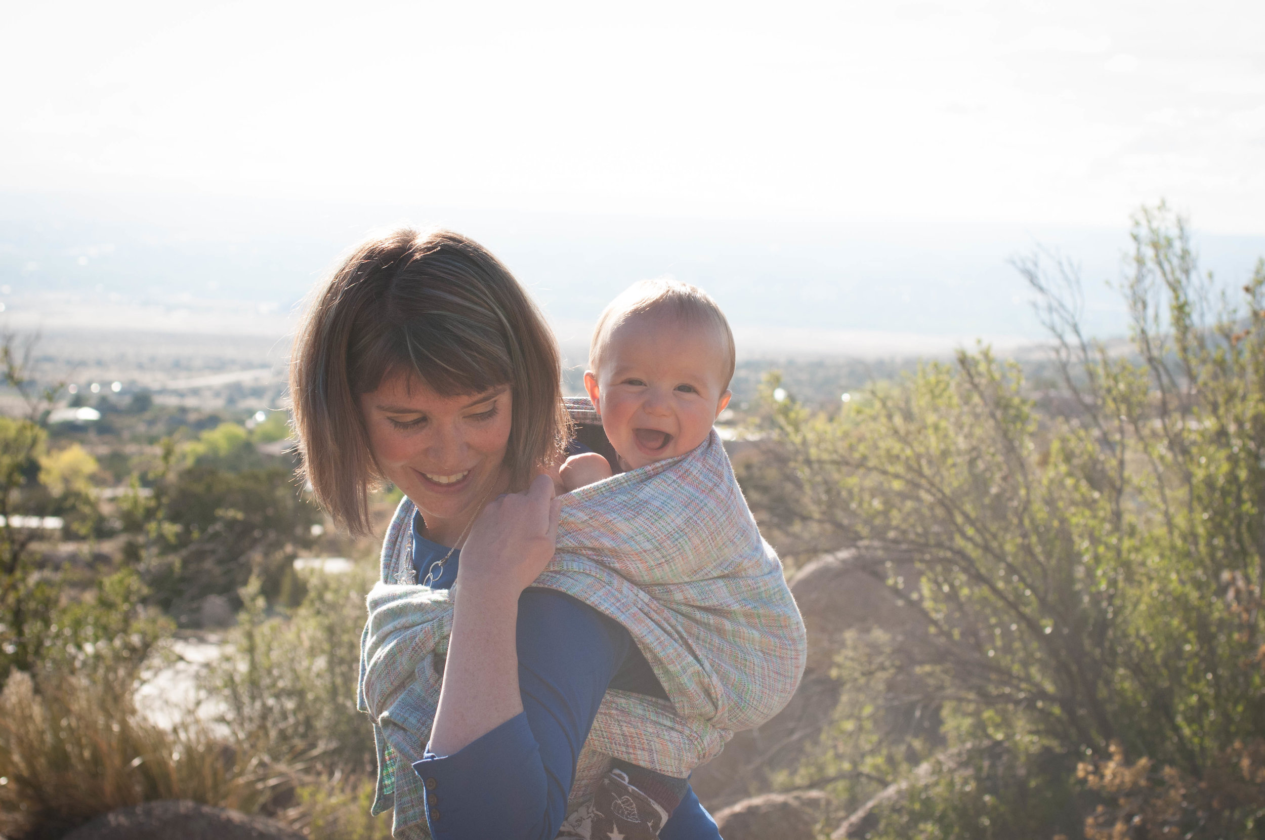 Image of Annie wearing her laughing baby on her back with a view overlooking Albuquerque, NM.