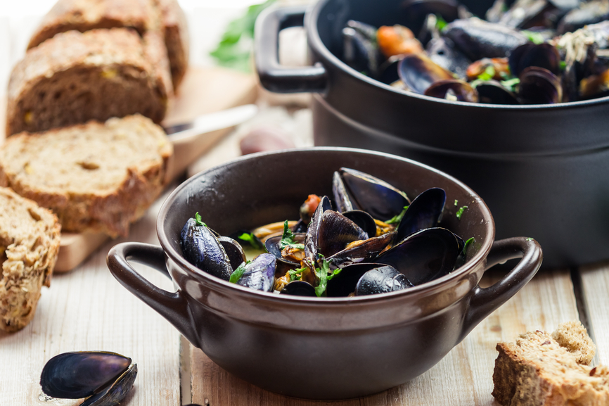 Mussels served in a sunny day with homemade bread