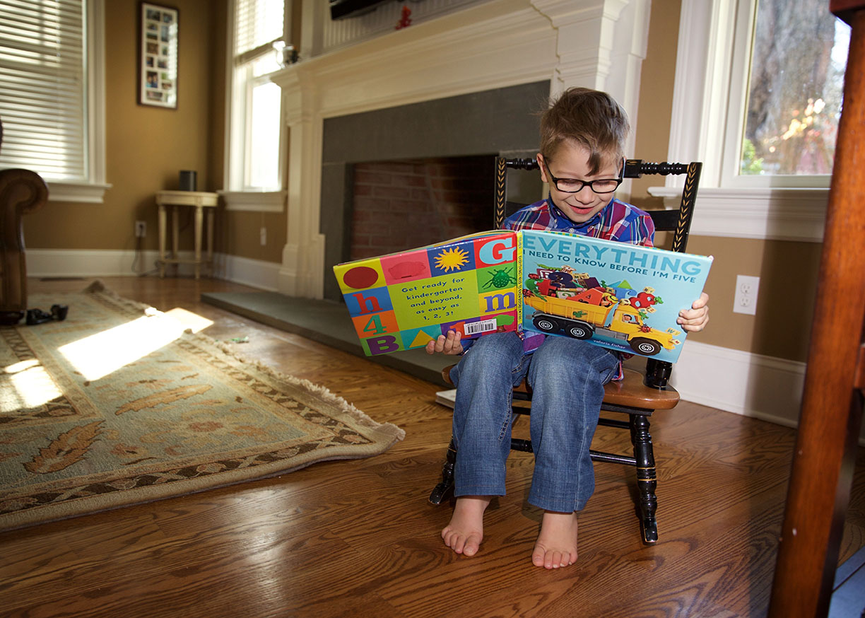 sweet boy in rocking chair reading everything to know before im five.jpg