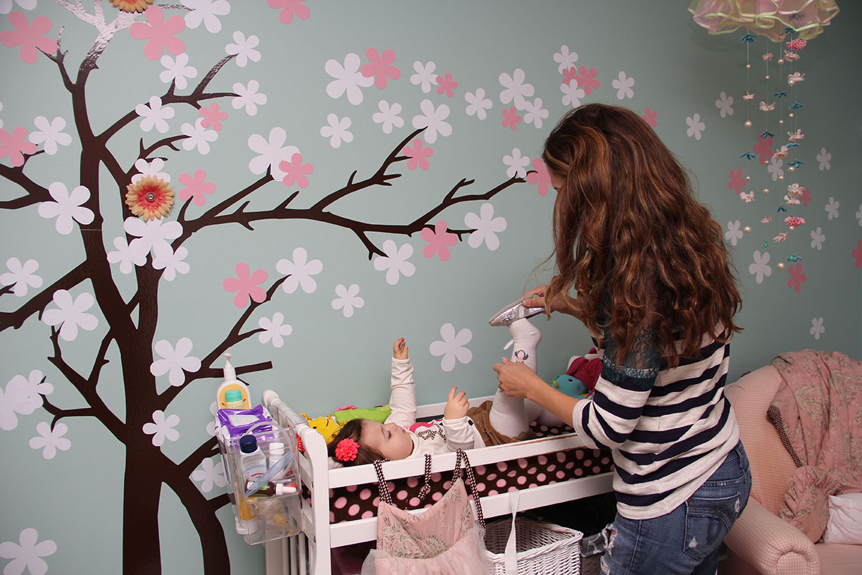 mother changing daughter in her room with cherry blossom wall decal.jpg