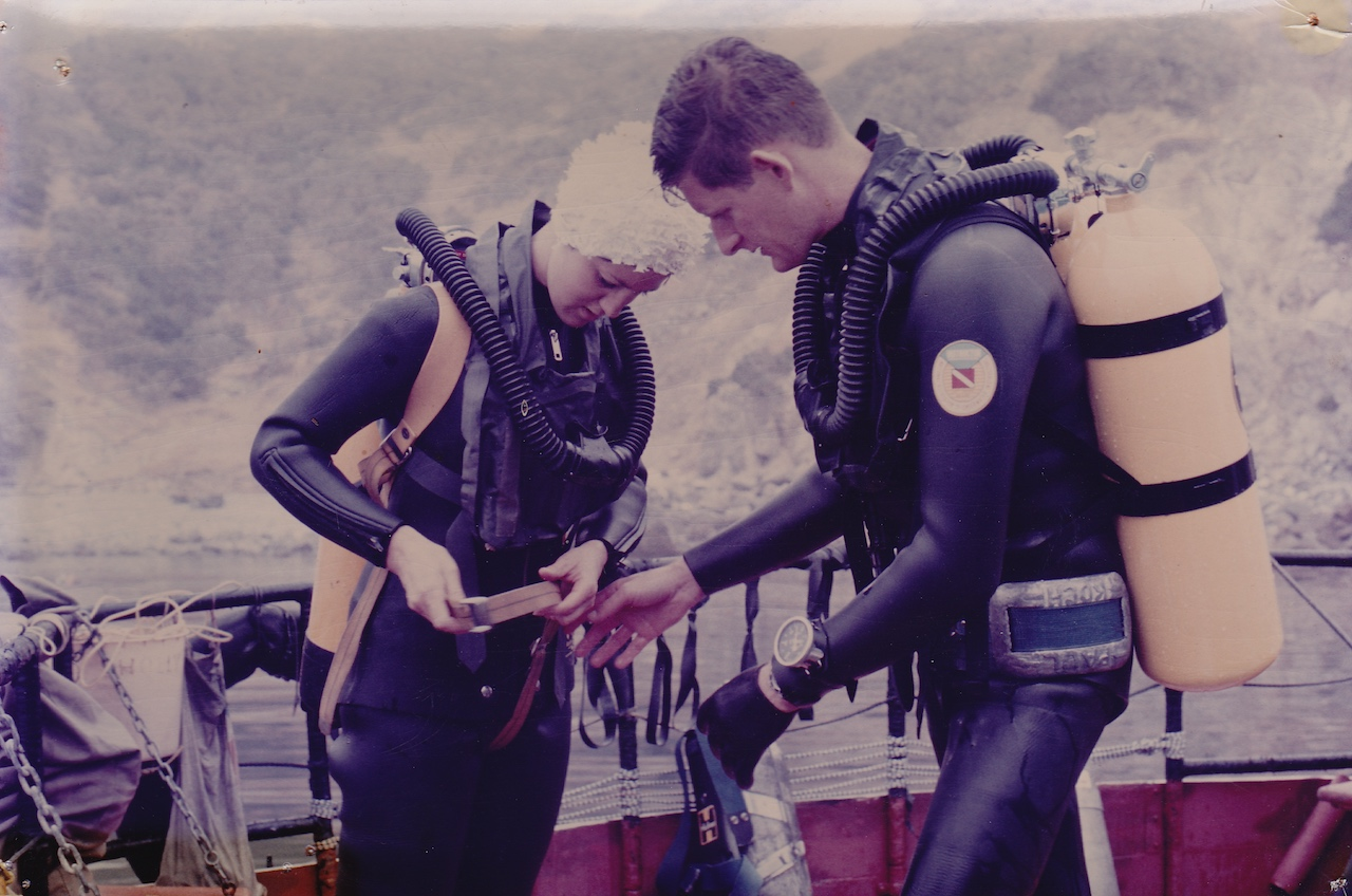 Tom, in early double hose regulator, helps a student with her gear for a dive at the Channel Islands.