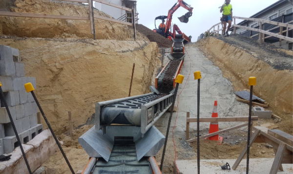 Loading Conveyors With A Digger Using A Hopper On A Building Site. NZ Conveyors