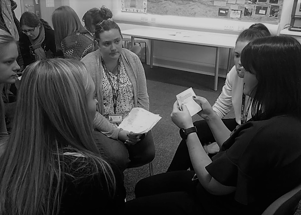 Two groups of five primary school teachers, each sitting in a circle on chairs in a classroom and discussing a card containing a philosophical prompt.