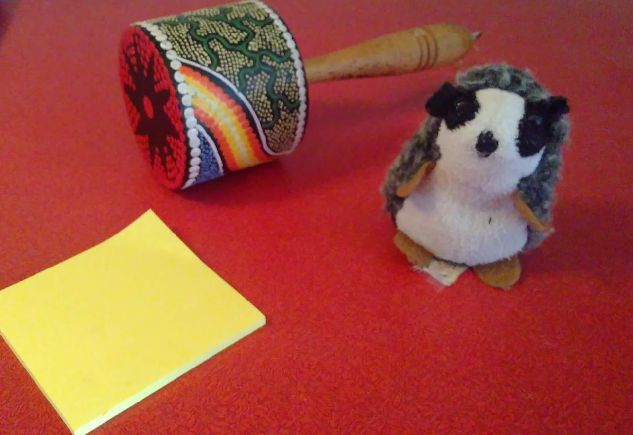Three assorted objects on a table (sticky notes, maracas, cuddly toy)