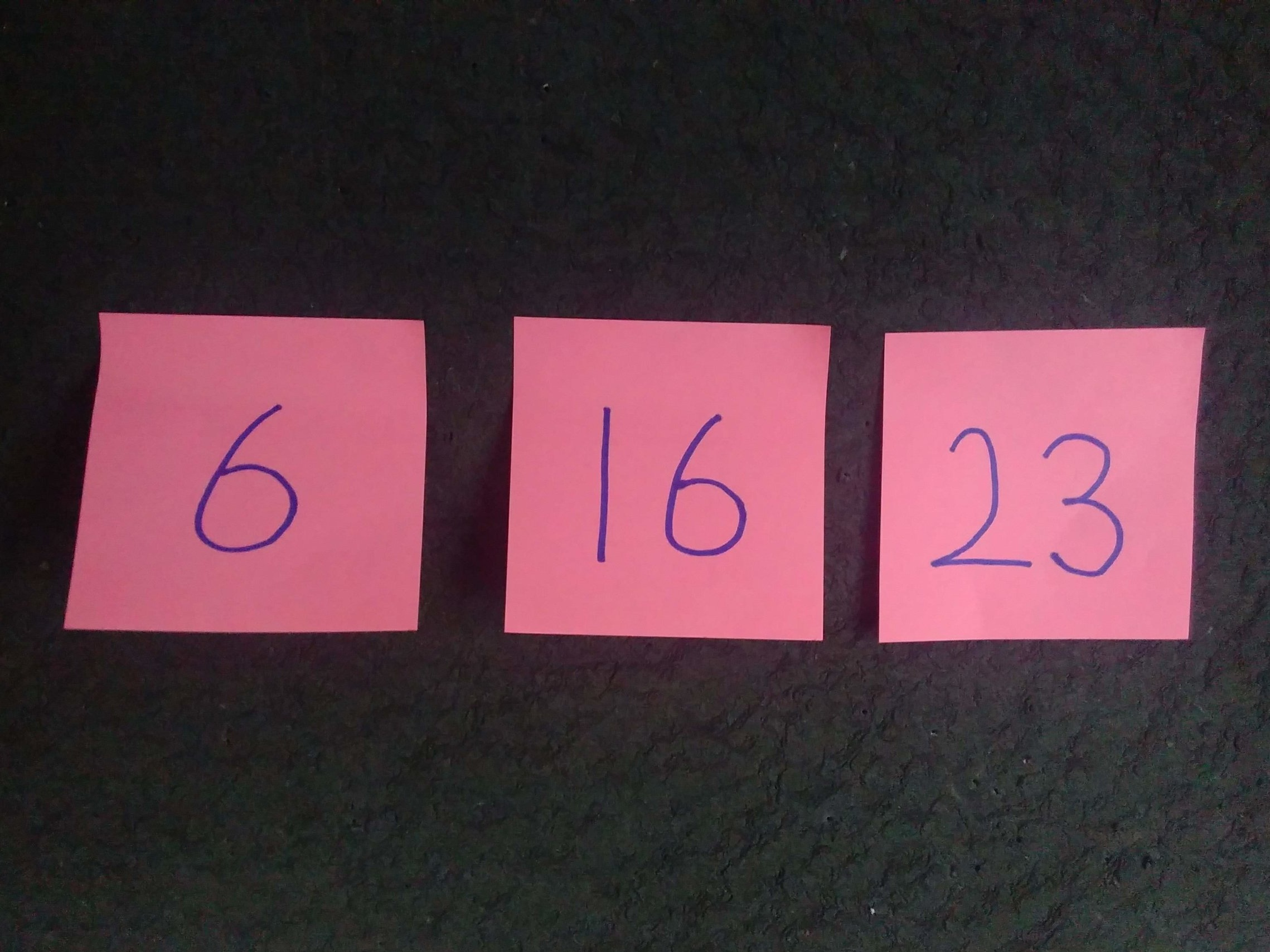 Three different numbers written on sticky notes