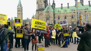 Nicholas participating in a protest to free Raif Badawi while articling at Amnesty Int'l.