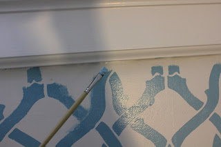 Hand-painting the stencil to meet the molding