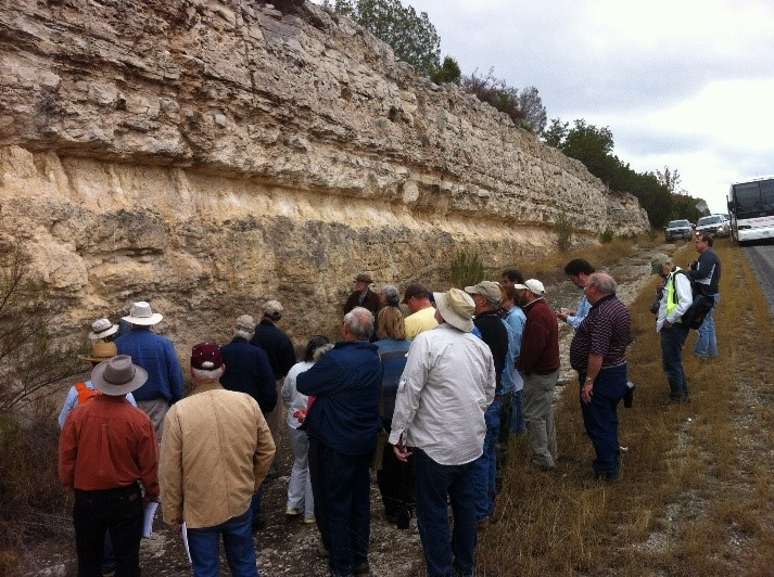 AGS members and trip leaders discuss the Edwards stratigraphy in the road cut along Interstate 10 east of Junction.