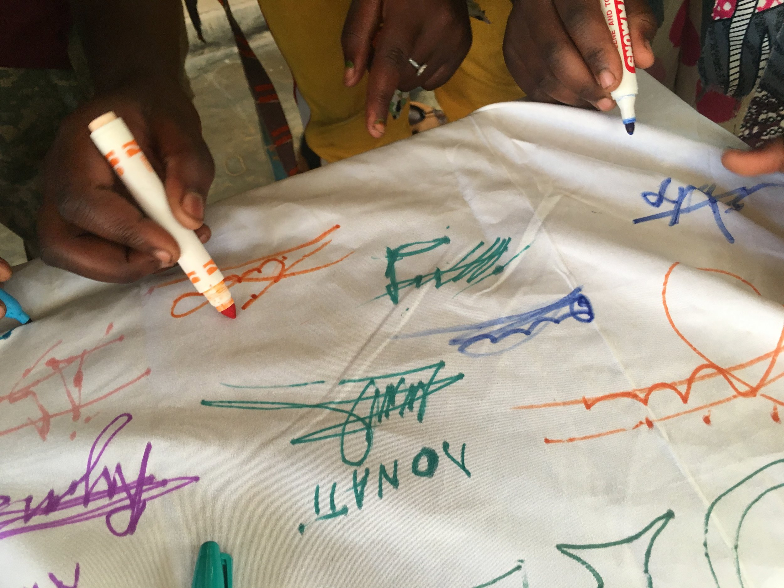 """Students signed a """"contract"""" committing to using their mosquito net every night to protect their families from malaria."""