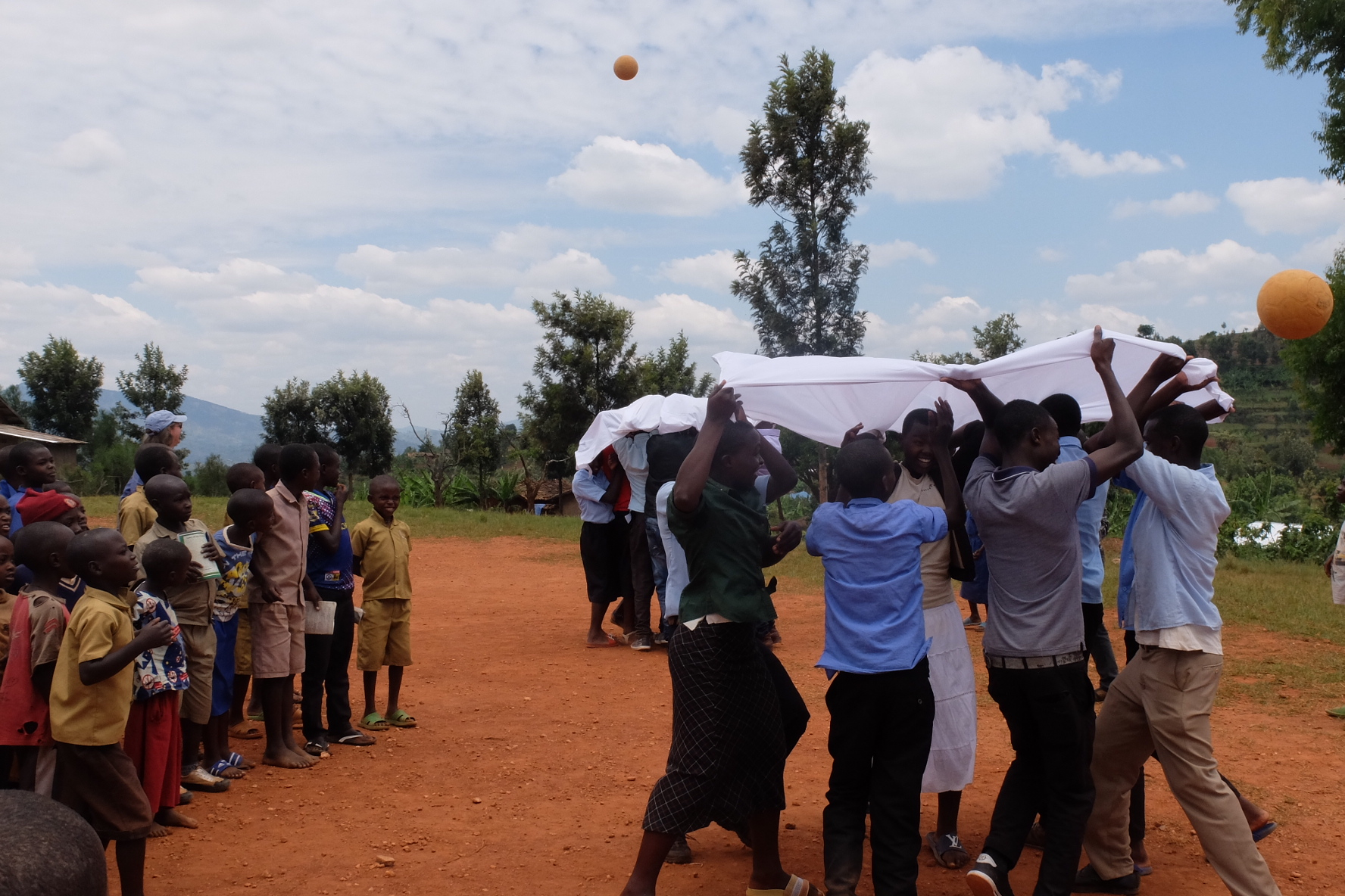 Students in Rwanda participate in behavior change focused mosquito net games at a STOMP Day Camp.