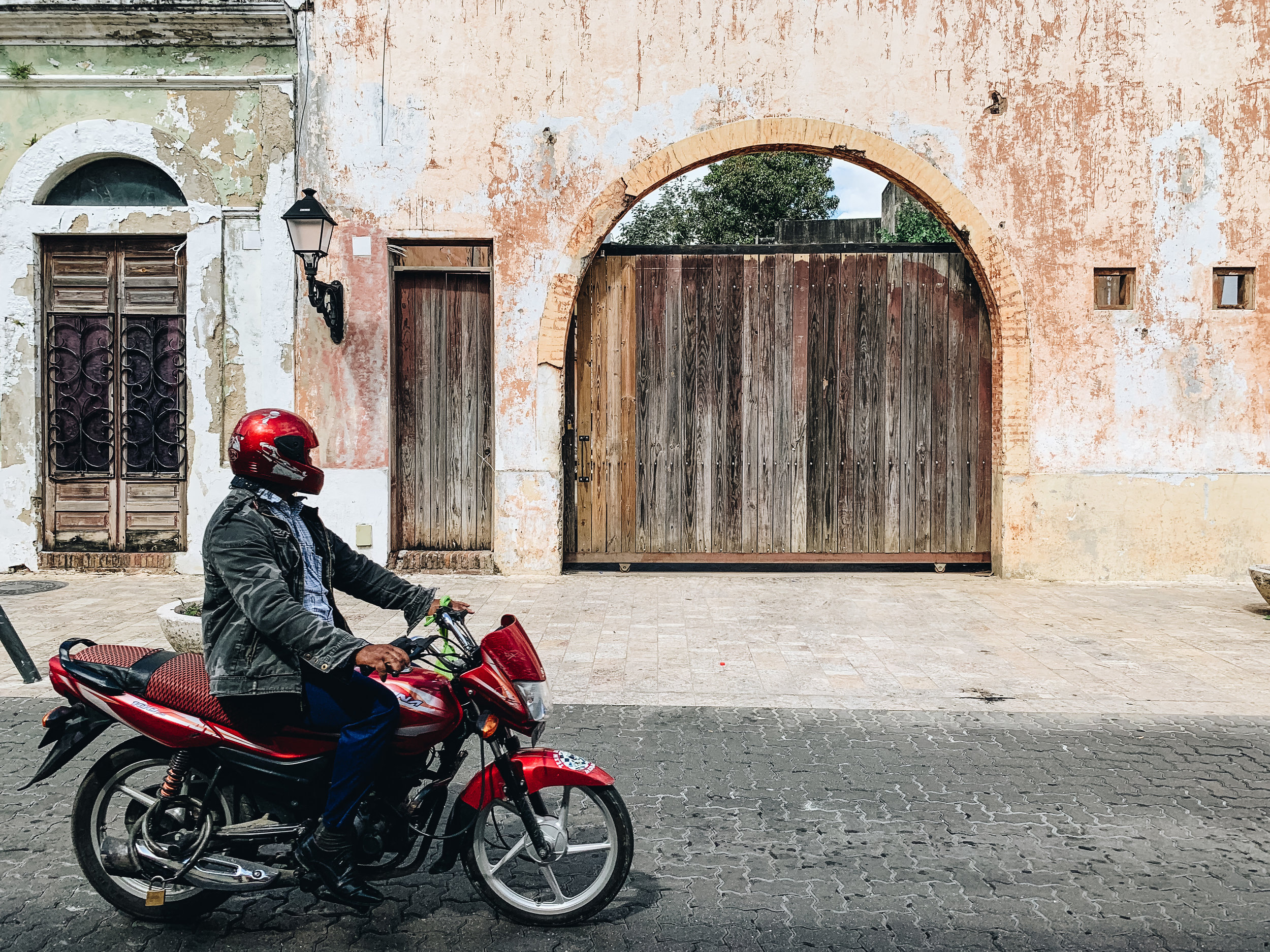 Biker's red toy stands out against peeling textures of old wall in Zona Colonial, Dominican Republic