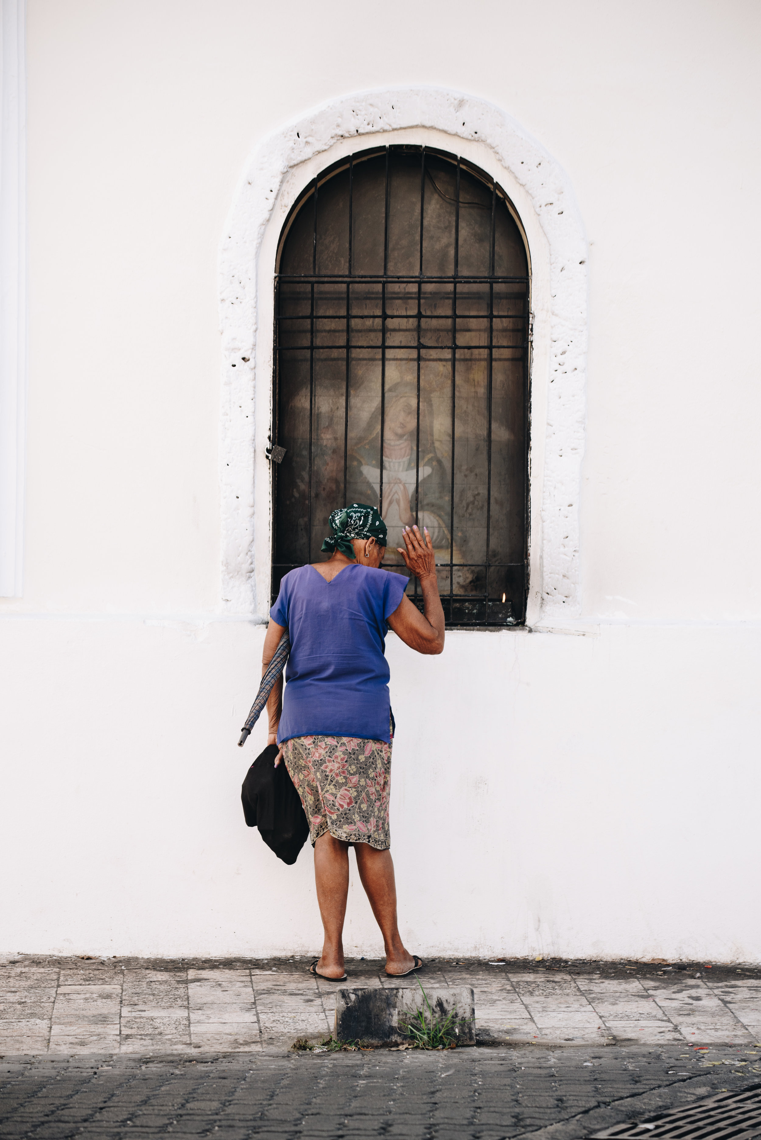 Woman pauses for prayer at church in Zona Colonial, Santo Domingo