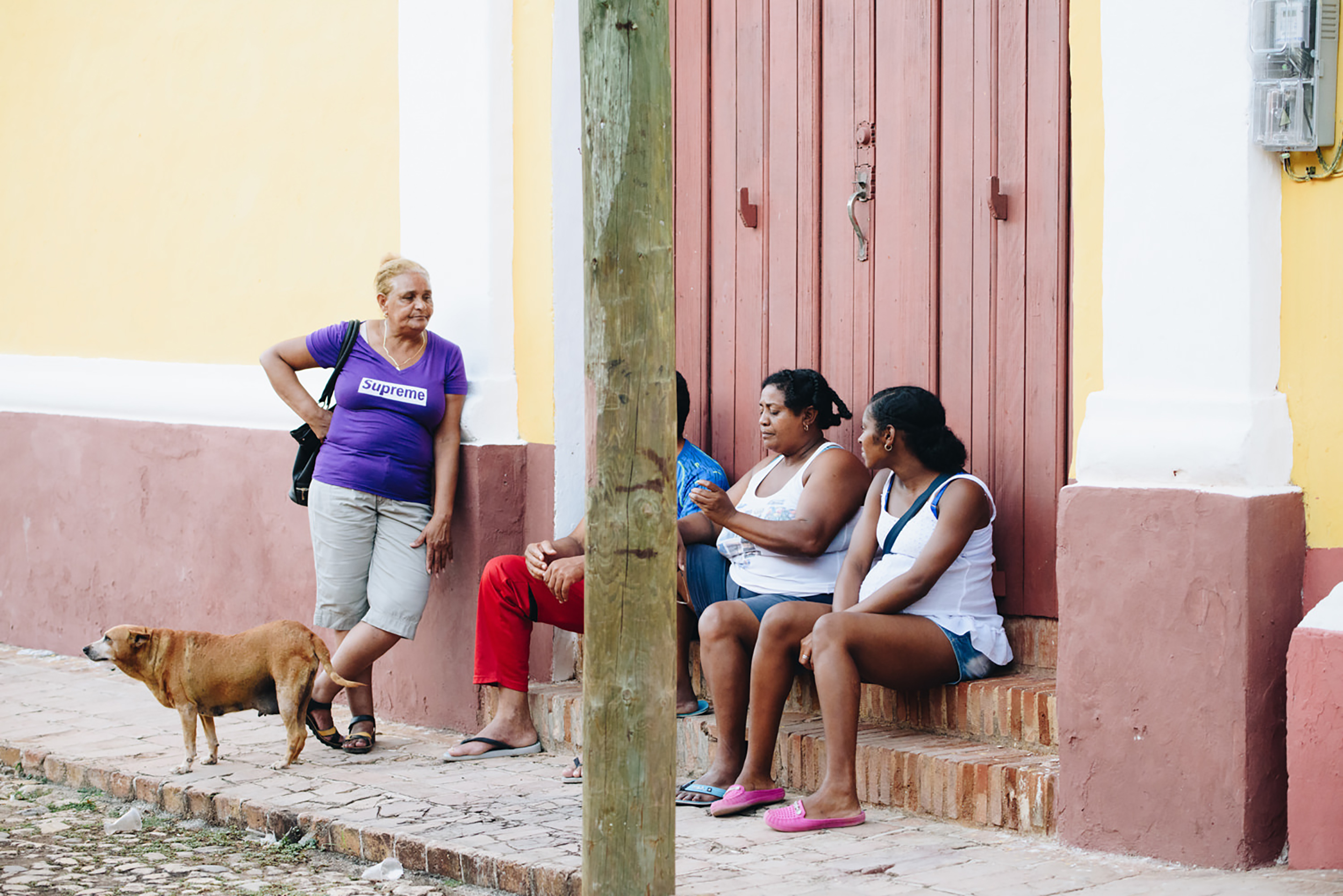Dog hangs out with ladies on a sidewalk in Cuba