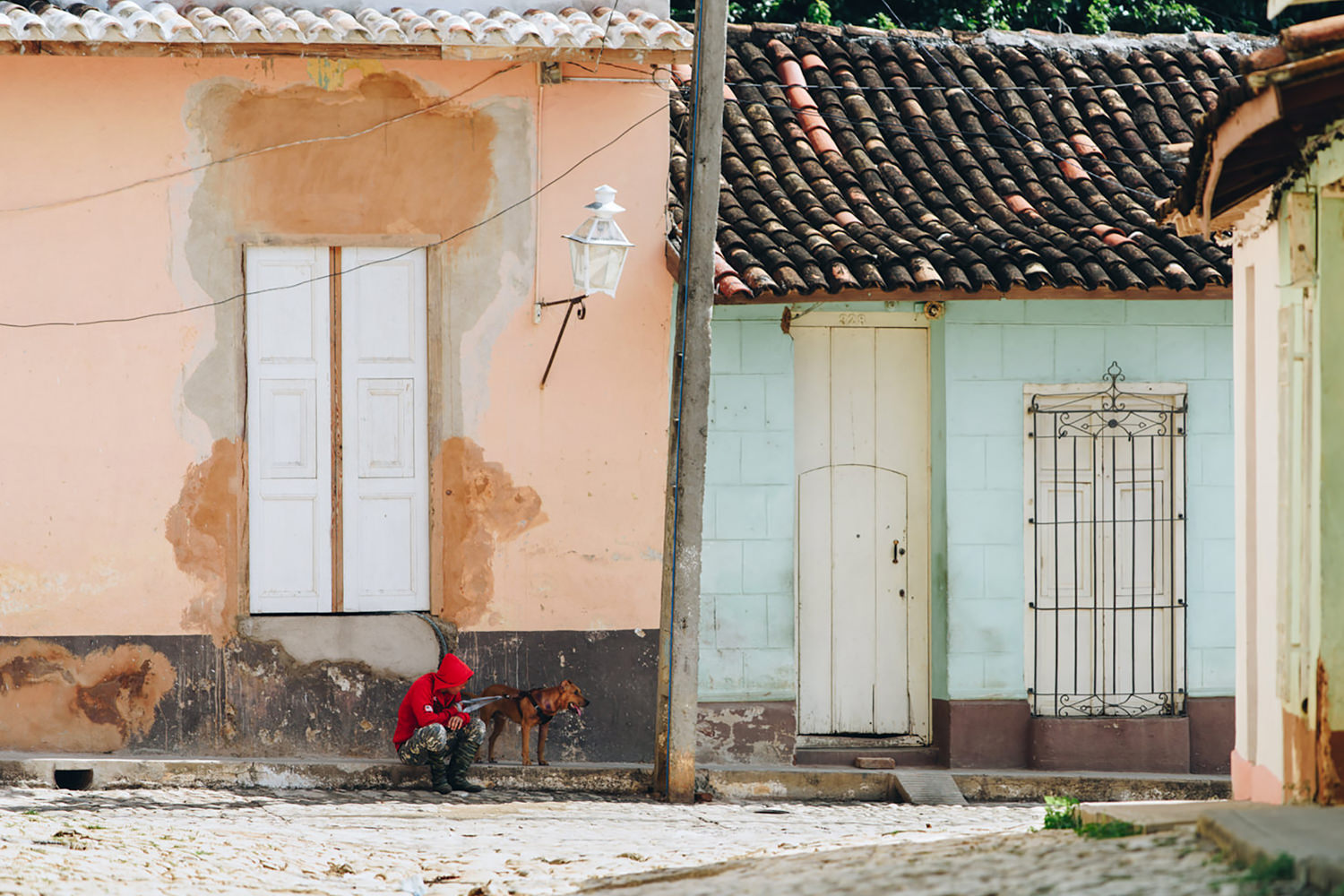 Dog and owner rests in shade on afternoon walk in Cuba