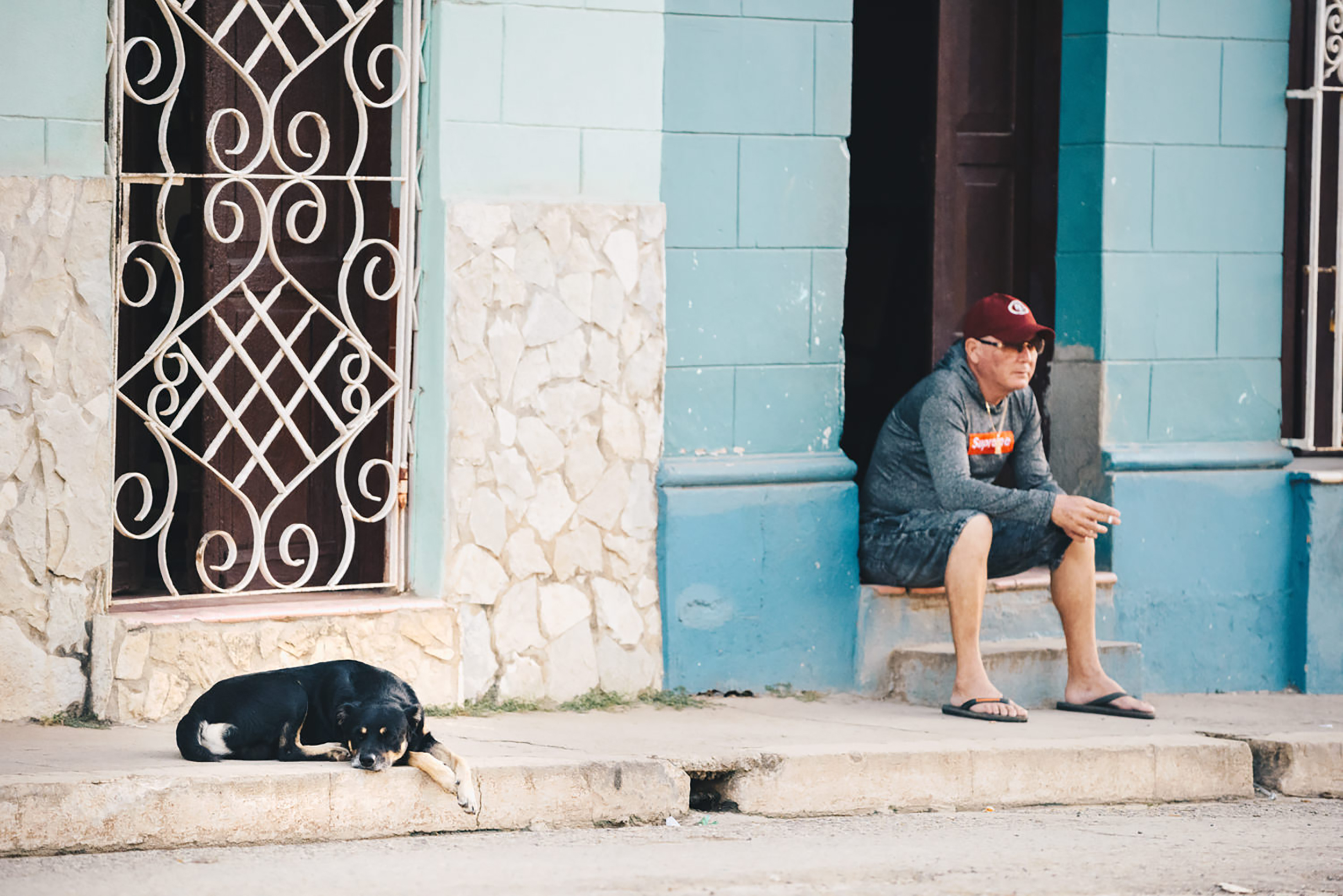 A dog rests on the sidewalk of a Cuban home.