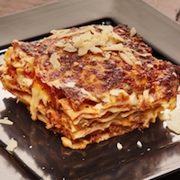 LASAGNE  Fresh-made lasagne sheets with bolognese and cream sauce topped with mozzarella cheese