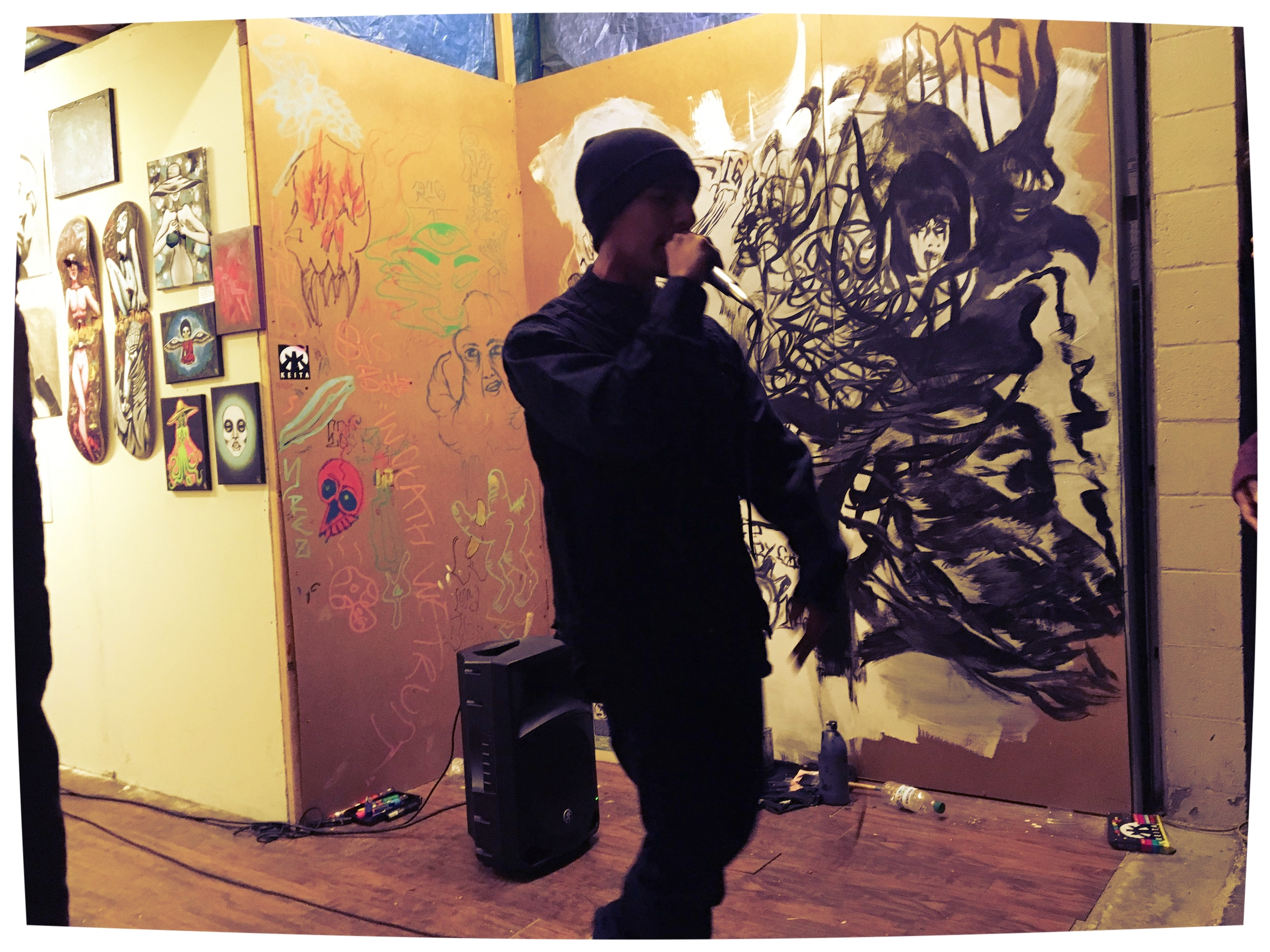 """The piece to the left of FUDAGOD was a shared effort by  Reaper 16 x Stucky 1 done live during the show. """"we want to vibe with the music, people, & flow... let the art evolve."""" STUCKY 1    < graffiti wall behind speaker. & art by BRUNA K. = 2 skateboards & 5 canvas  >"""