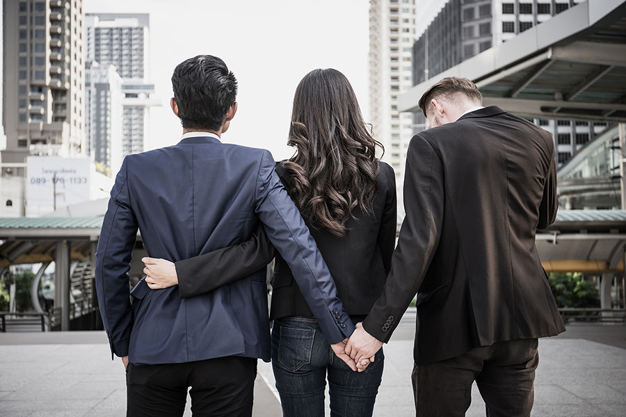 Three people wearing suits with their backs towards the camera