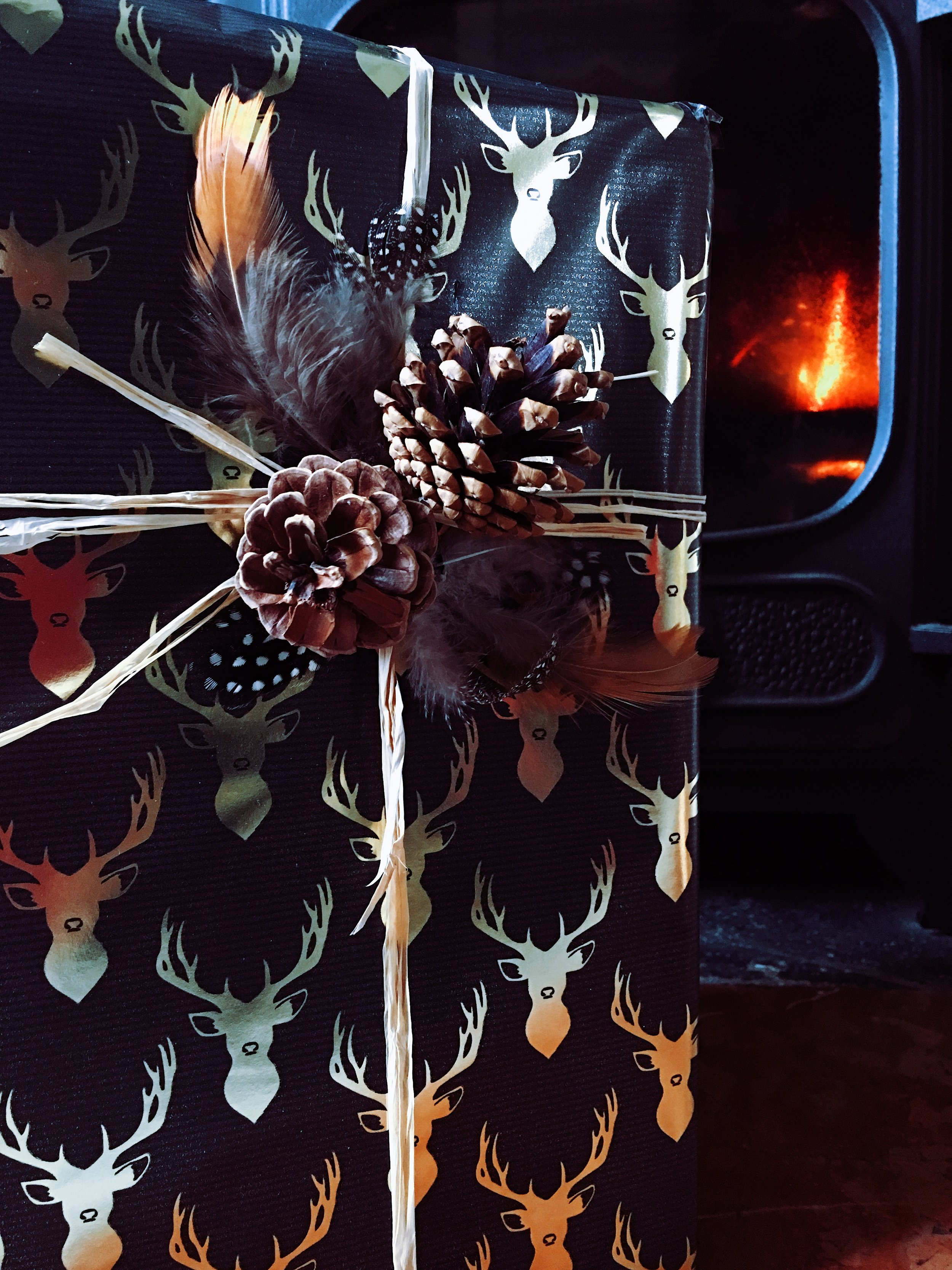 Black and gold wrapping paper by Sainsbury's. Raffia and feathers from Hobbycraft. Fir cones collected from Epping forest!
