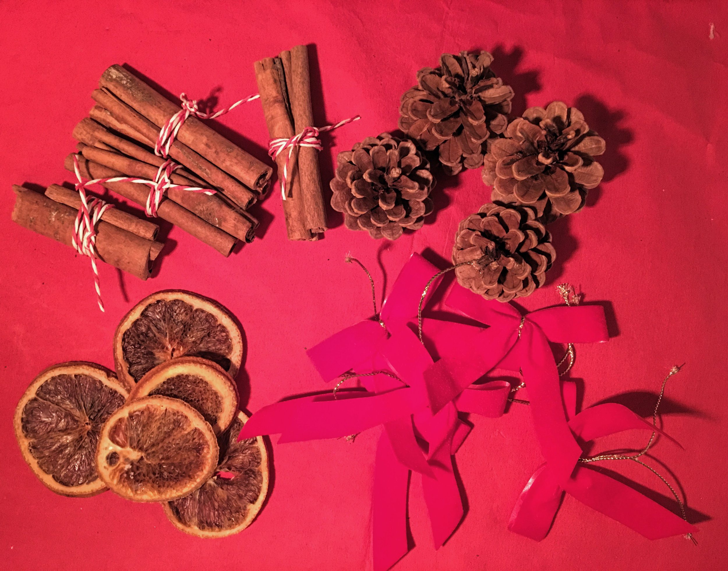 Along with your dehydrated orange slices and cinnamon sticks, use fir cones and red velvet bows.