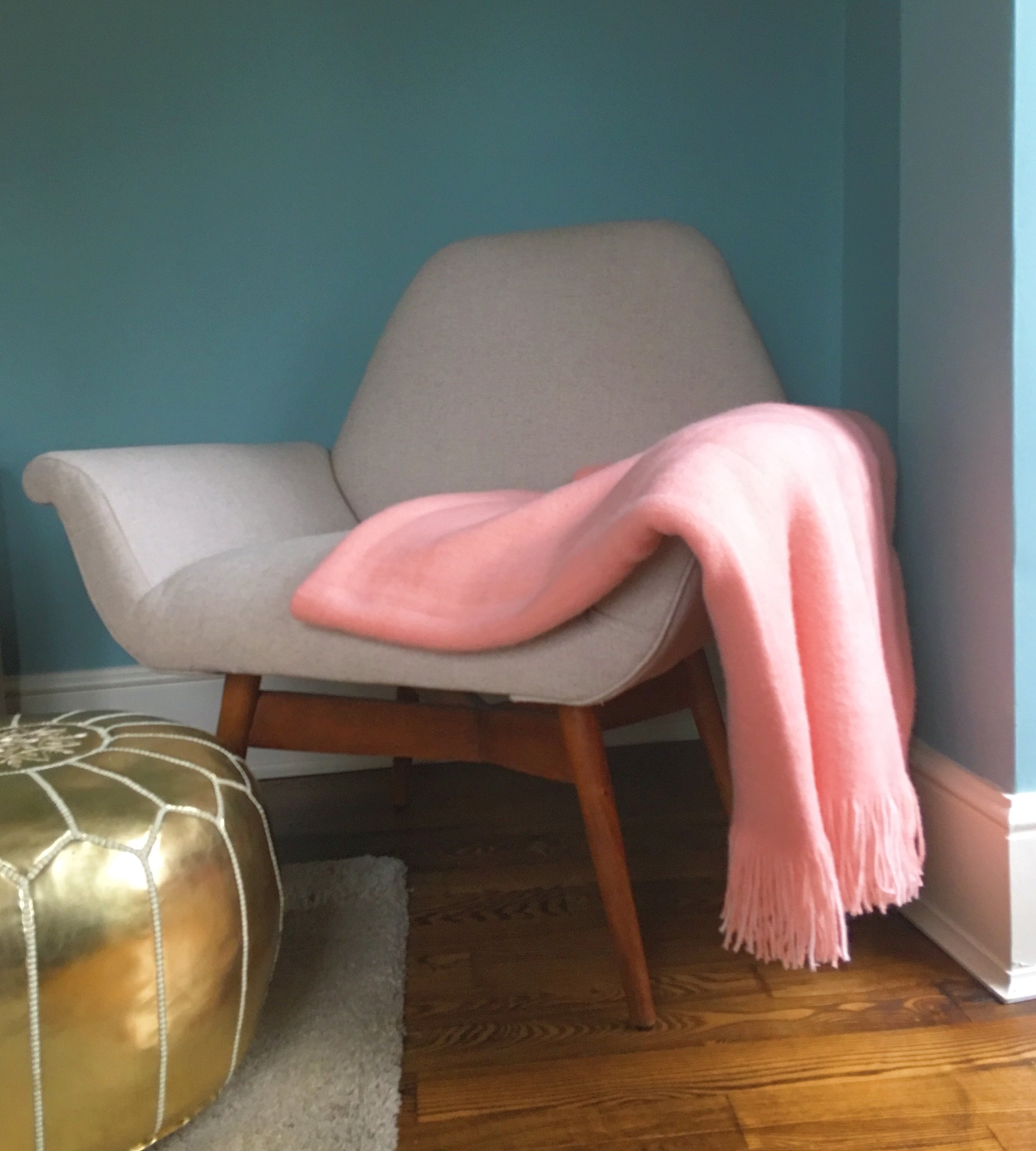 My pink throw at home complements my blue walls in my living room.