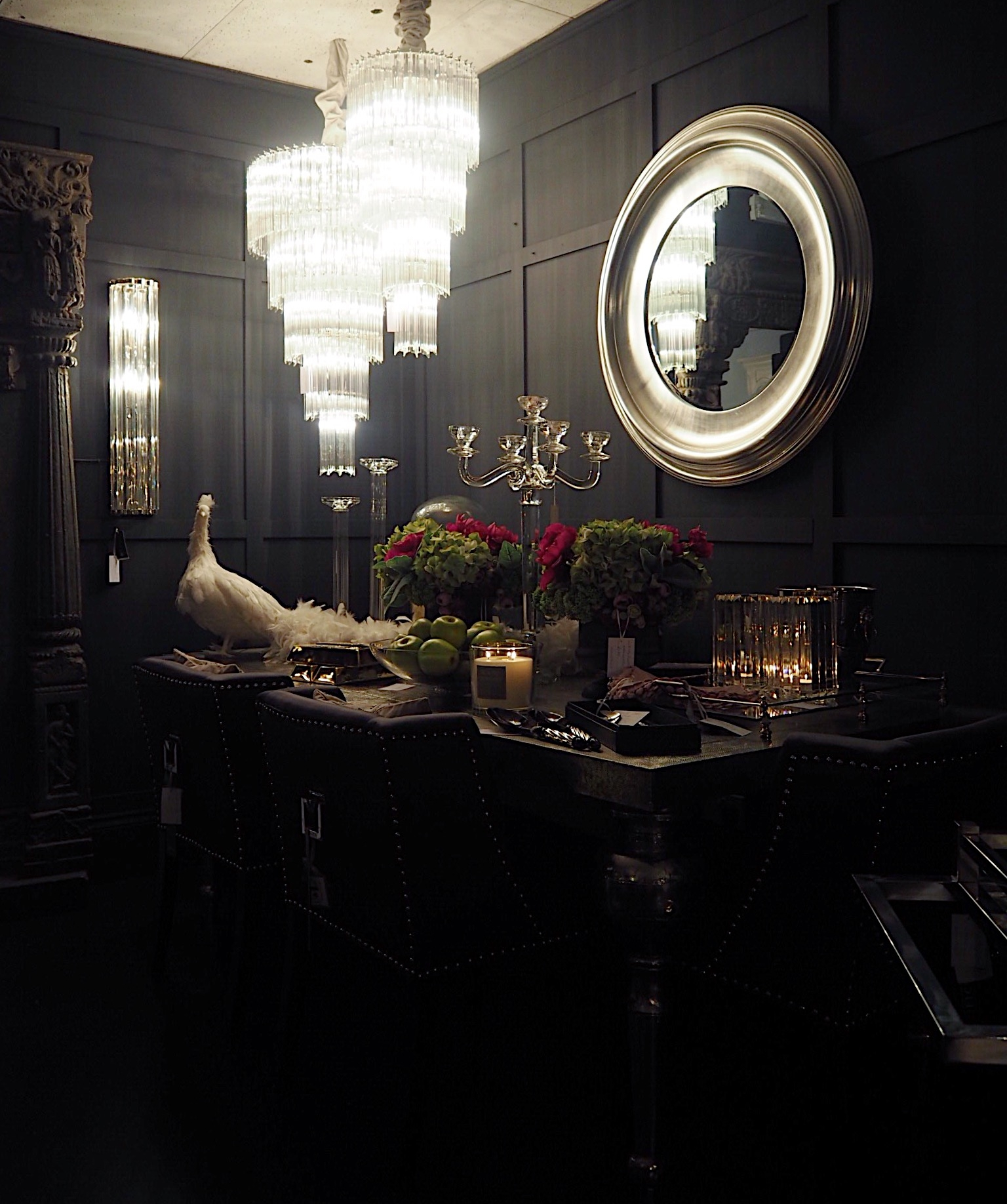 The dark background in the Sweetpea & Willow showroom frames the wall mirror and items on the table perfectly.