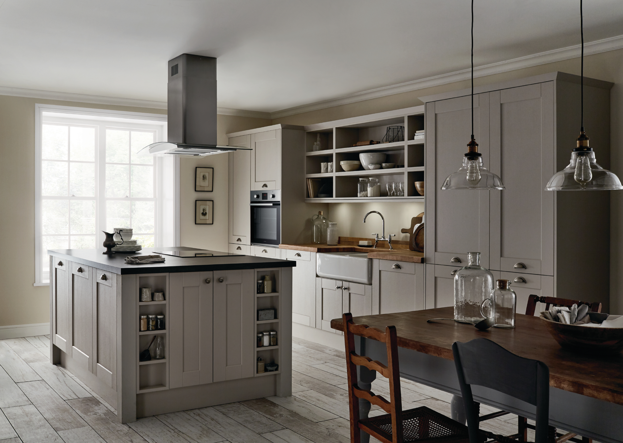 Howdens Fairford kitchen in Cashmere, featuring pewter effect cabinet handles, blackstone and solid oak block worktop and upstand, Lamona single oven, ceramic hob and curved glass island extractor, Lamona double Belfast sink and Lamona Victorian Bridge tap. All available via Howdens.